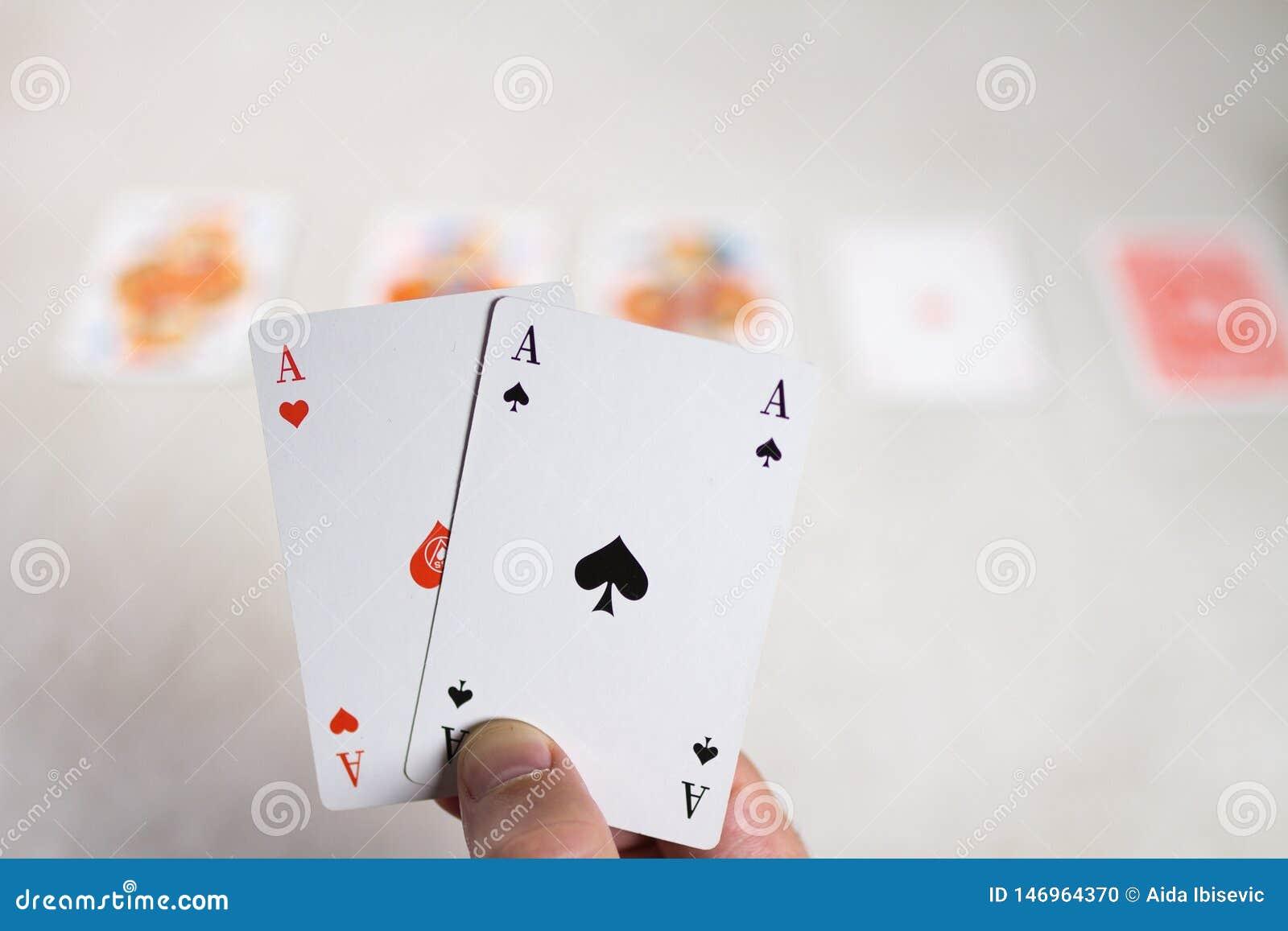 Ás da terra arrendada dois da mão na frente de outros cartões
