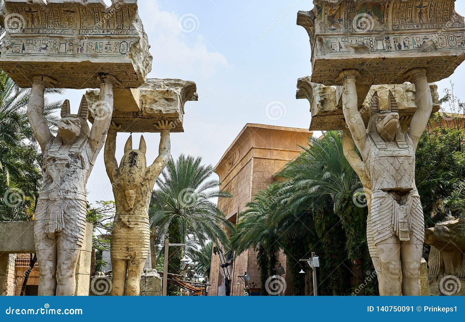 Ägyptische Statuen, welche die großen Flusssteine geschrieben mit Hieroglyphen an Unversals-Studios Singapur anheben