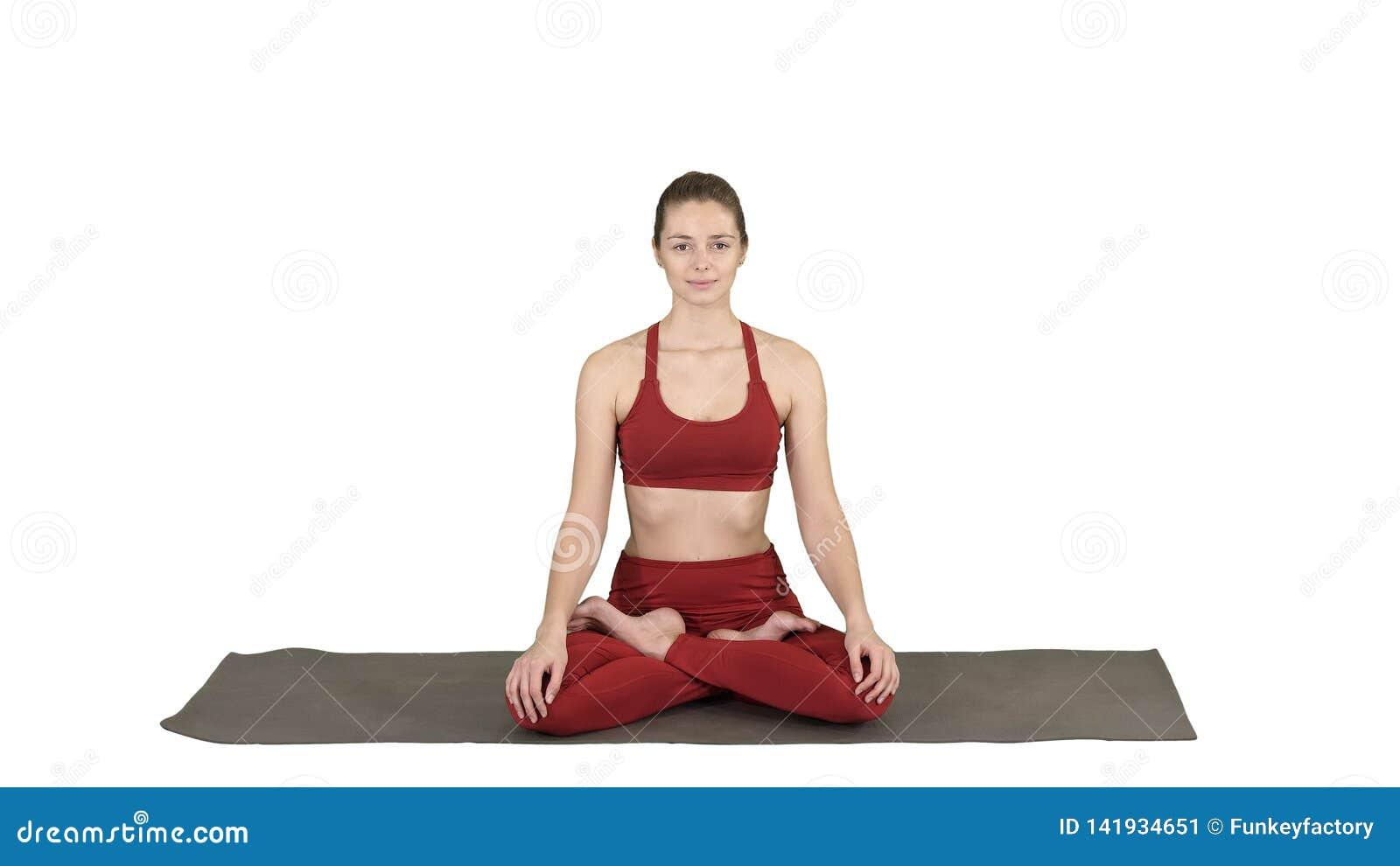 Übendes Yoga der sportlichen attraktiven Frau, sitzend in Lotus-Übung, Siddhasana-Haltung, die auf weißem Hintergrund atmet