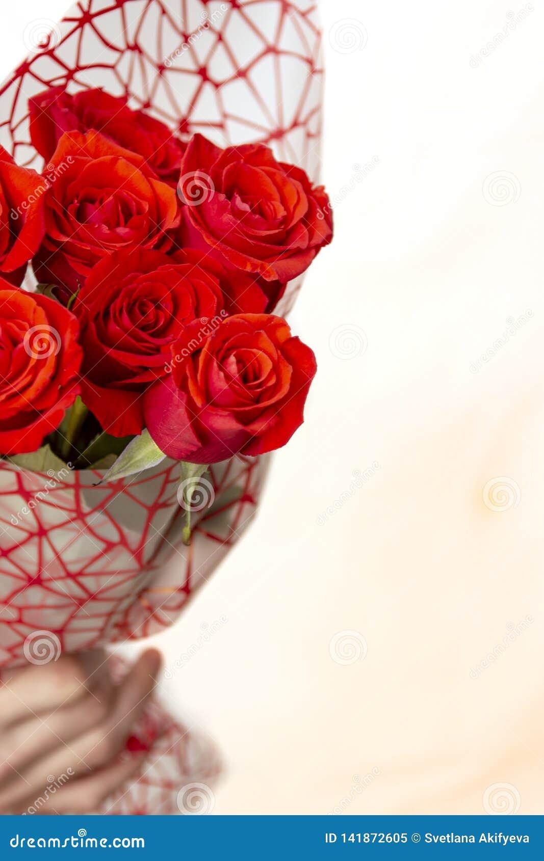 Übergeben Sie das Halten des Blumenstraußes der roten Rosen über weißem Hintergrund