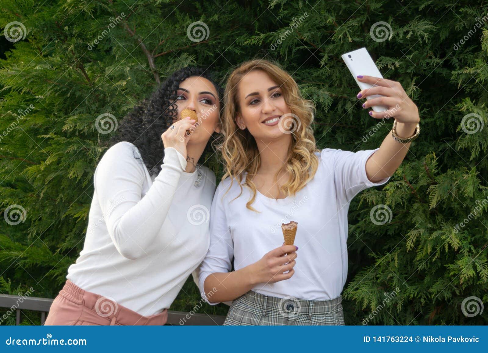 两个女孩采取selfies并且吃着冰淇淋