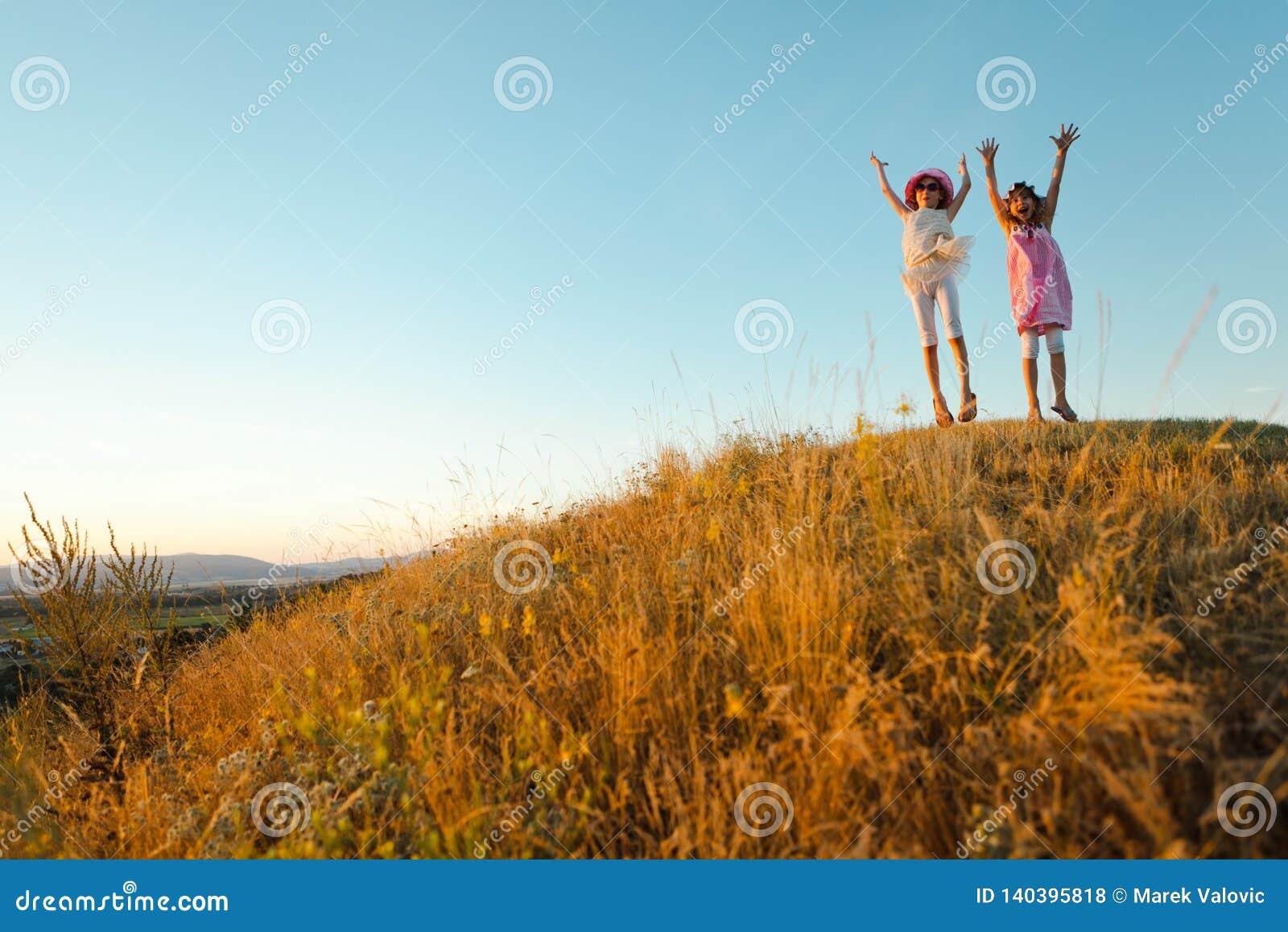两个快乐的孩子在夏日以后跳并且举了-日落的手