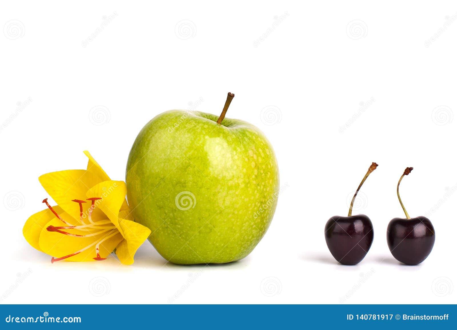 两个樱桃莓果和一个大绿色苹果在白色背景被隔绝的关闭宏指令