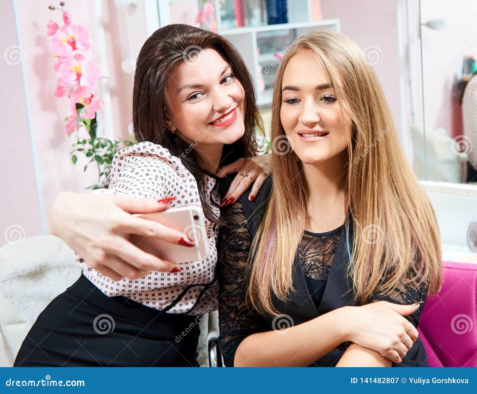 两个深色的女孩和金发碧眼的女人做在发廊的一selfie