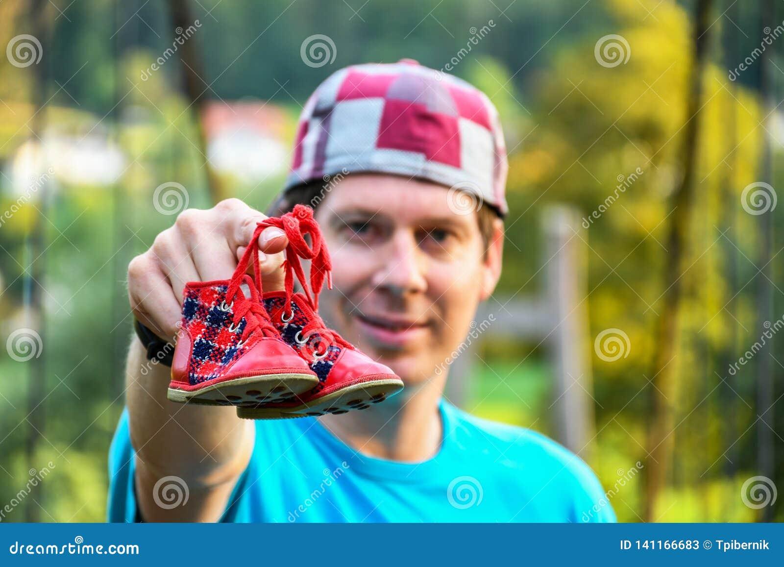 举行在两双延长的胳膊小红色童鞋的少女