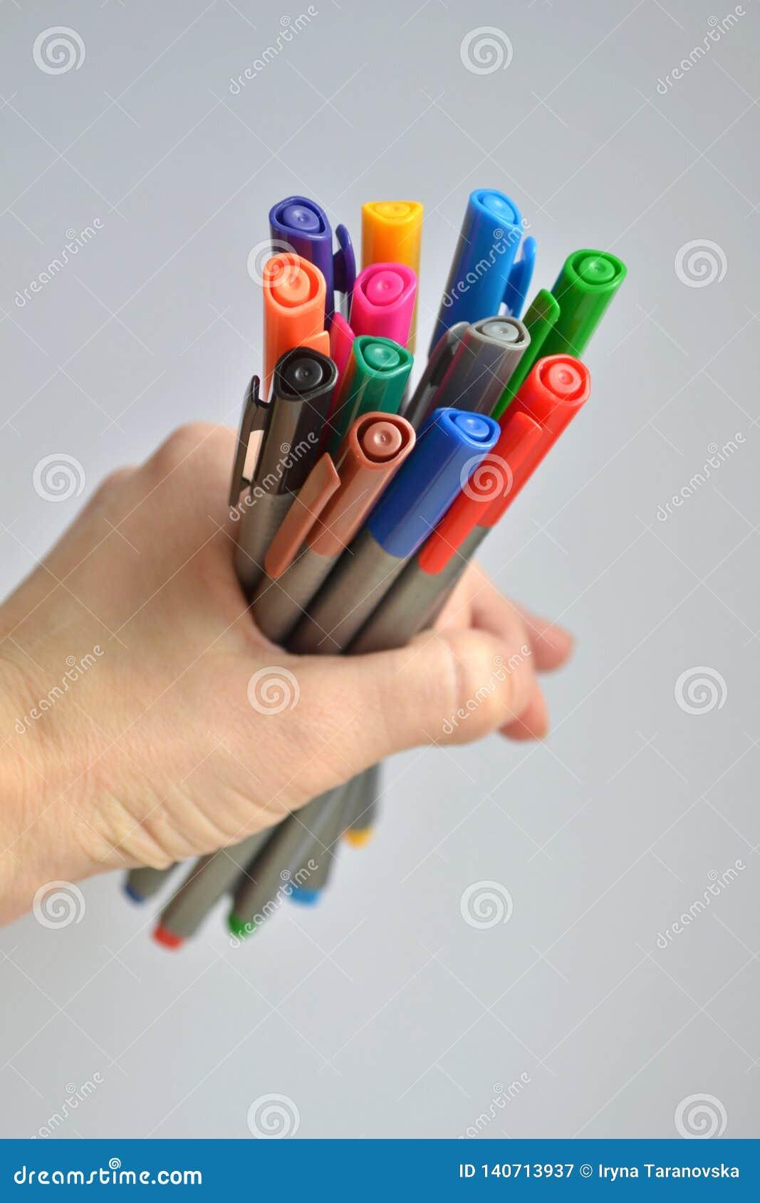 举行在妇女的手上的设置多彩多姿的笔,在灰色背景,垂直针对
