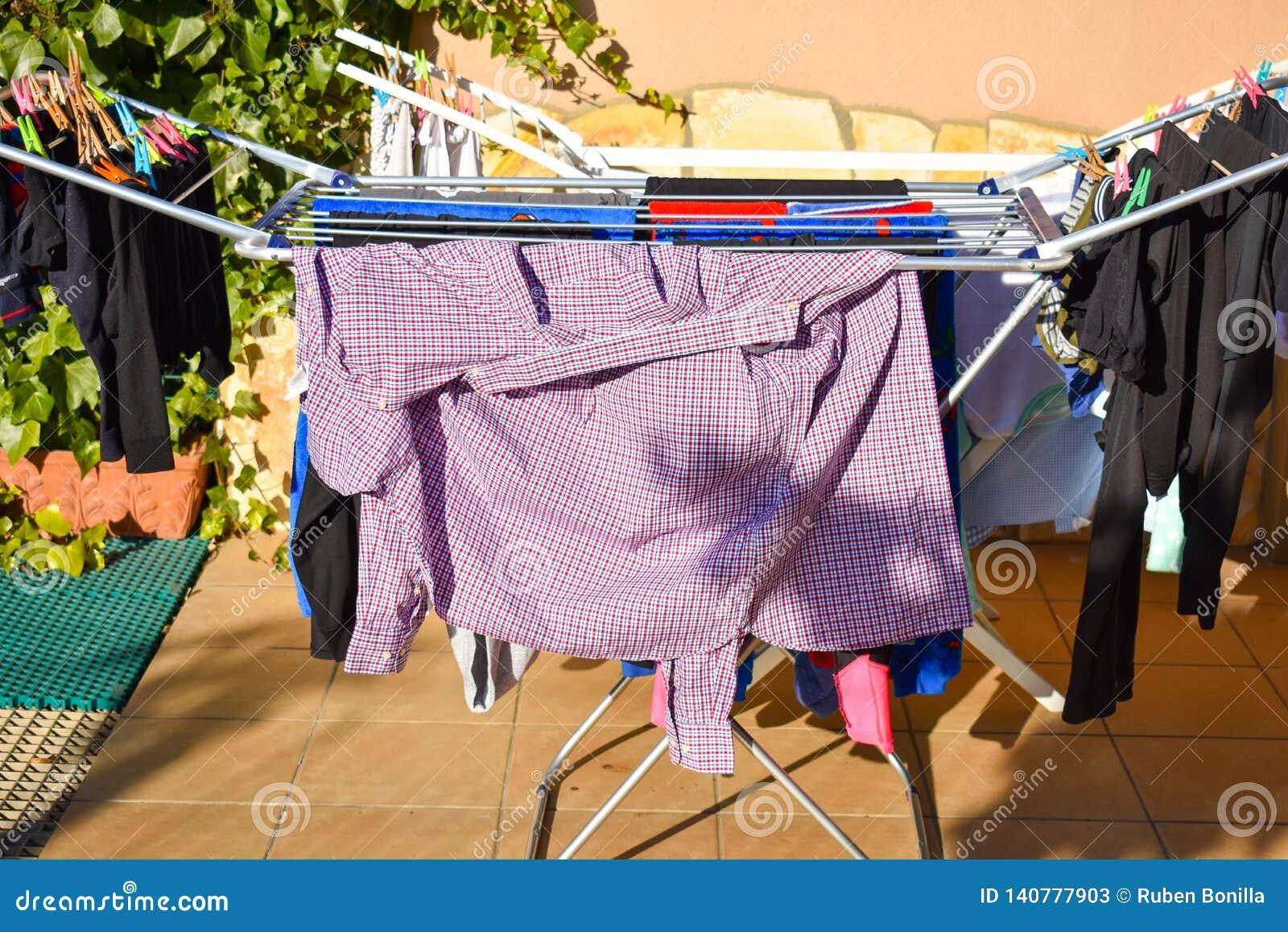 举行在洗涤的线的许多不同的衣裳在一个庭院在一好日子
