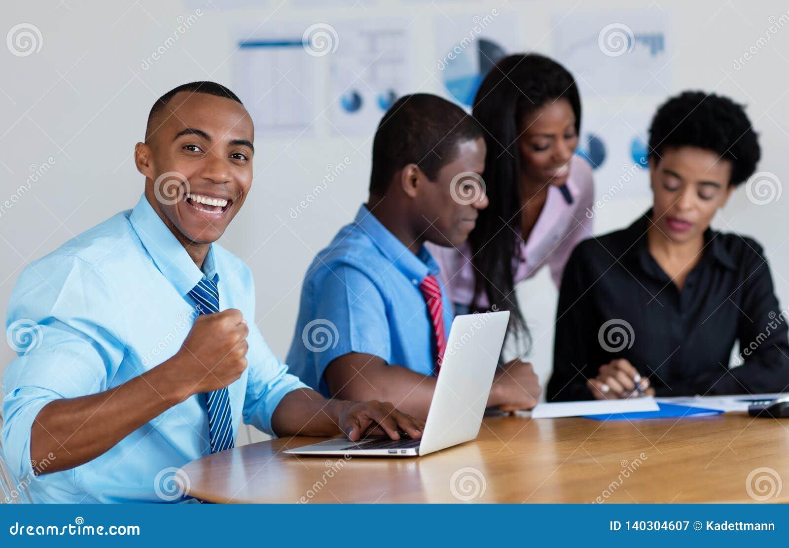 与企业队的愉快的非裔美国人的商人在办公室
