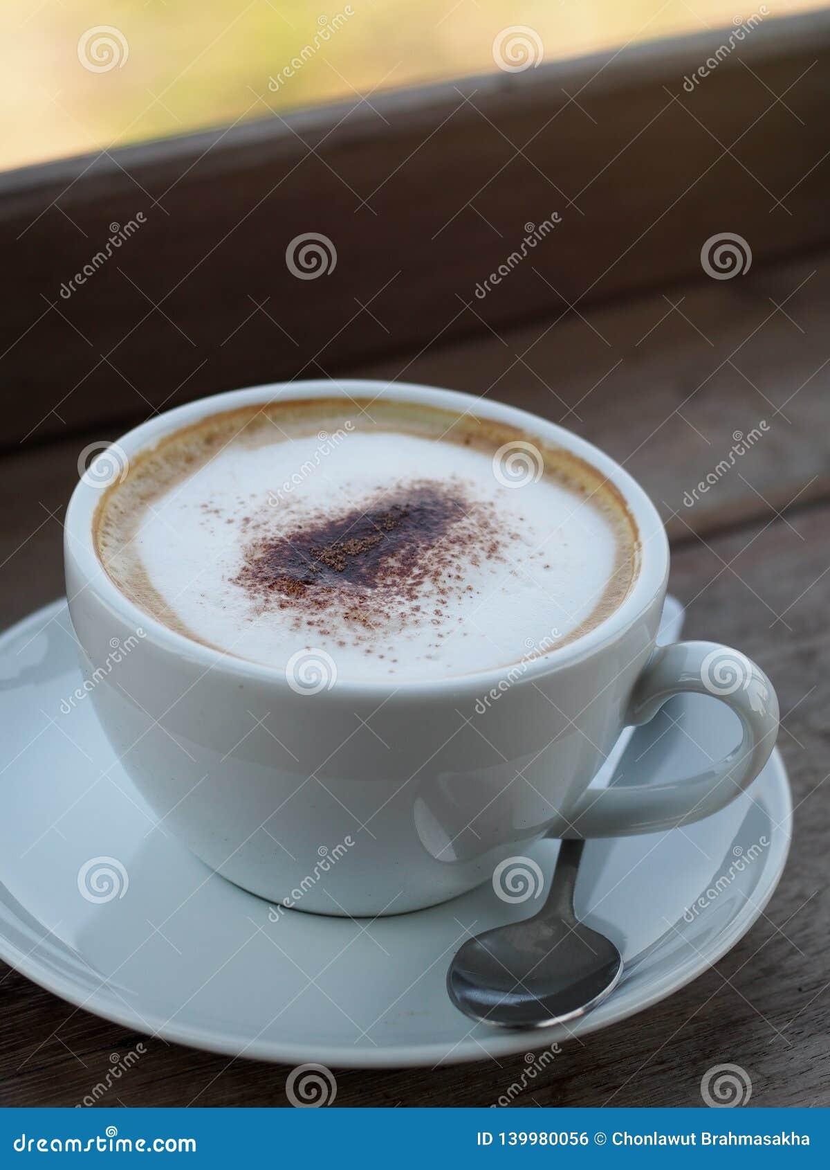 与奶油色充分的美好的泡影的热的热奶咖啡一点可可粉在白色陶瓷咖啡杯服务