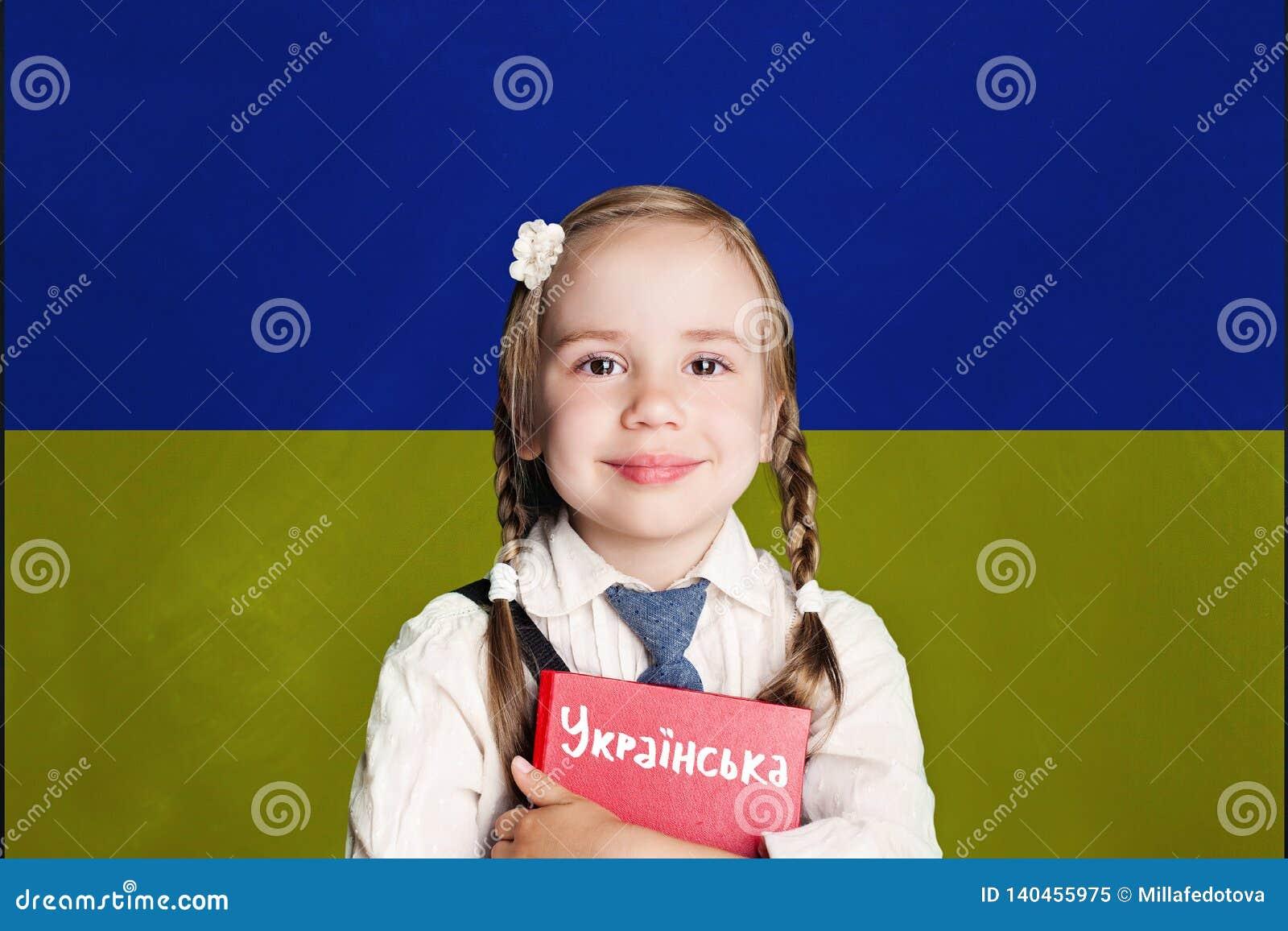 与孩子女孩女学生的乌克兰概念有在乌克兰旗子背景的红色书的 学会乌克兰语语言