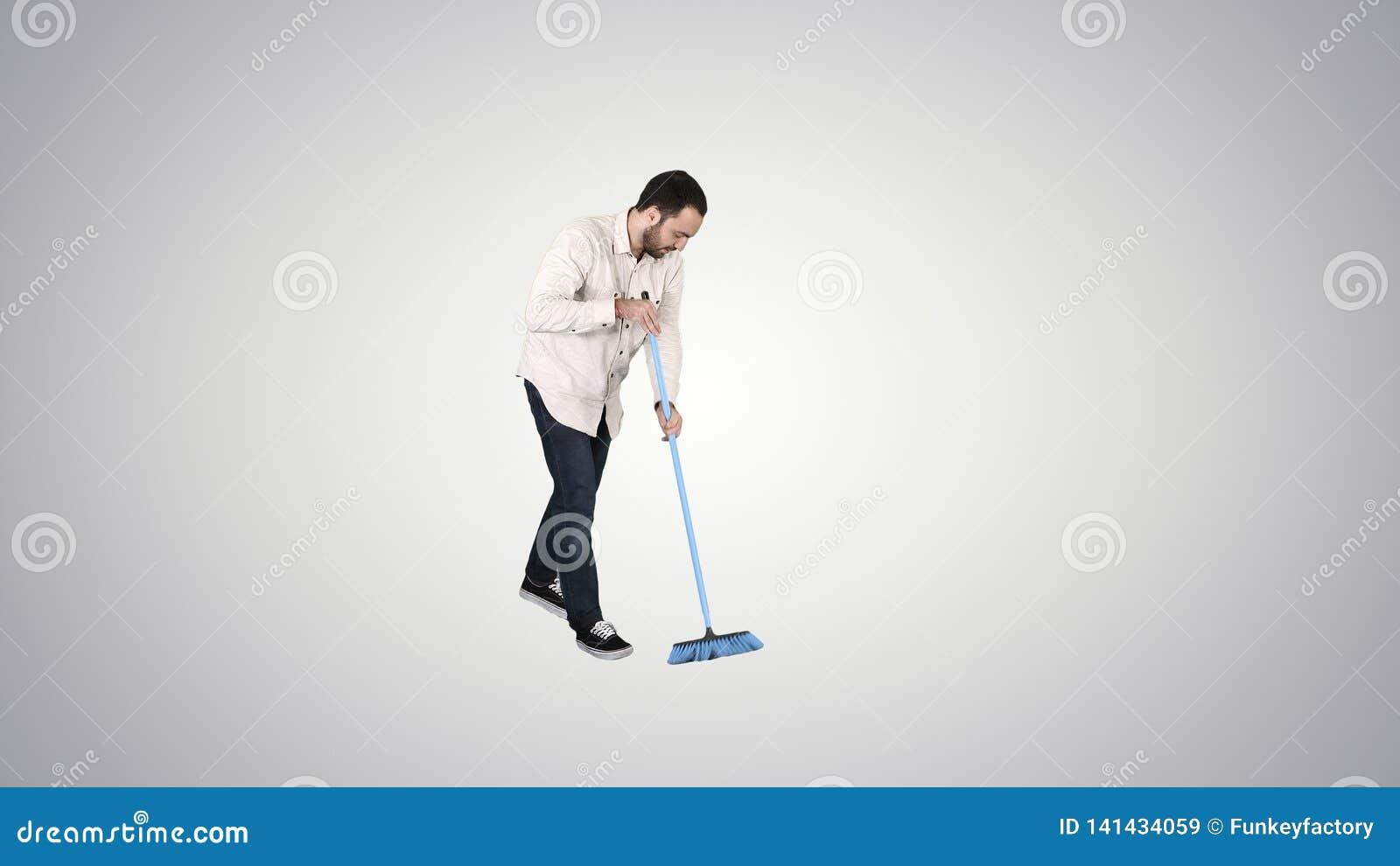 与刷子的年轻人清洗的地板在梯度背景