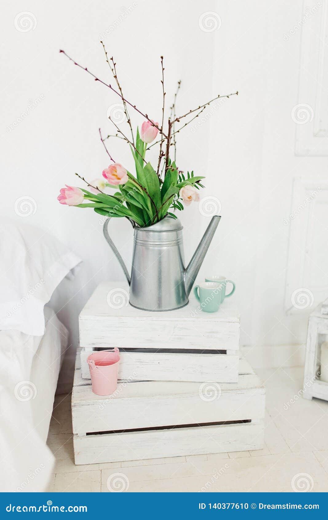与桃红色郁金香的锌喷壶在白色背景在卧室