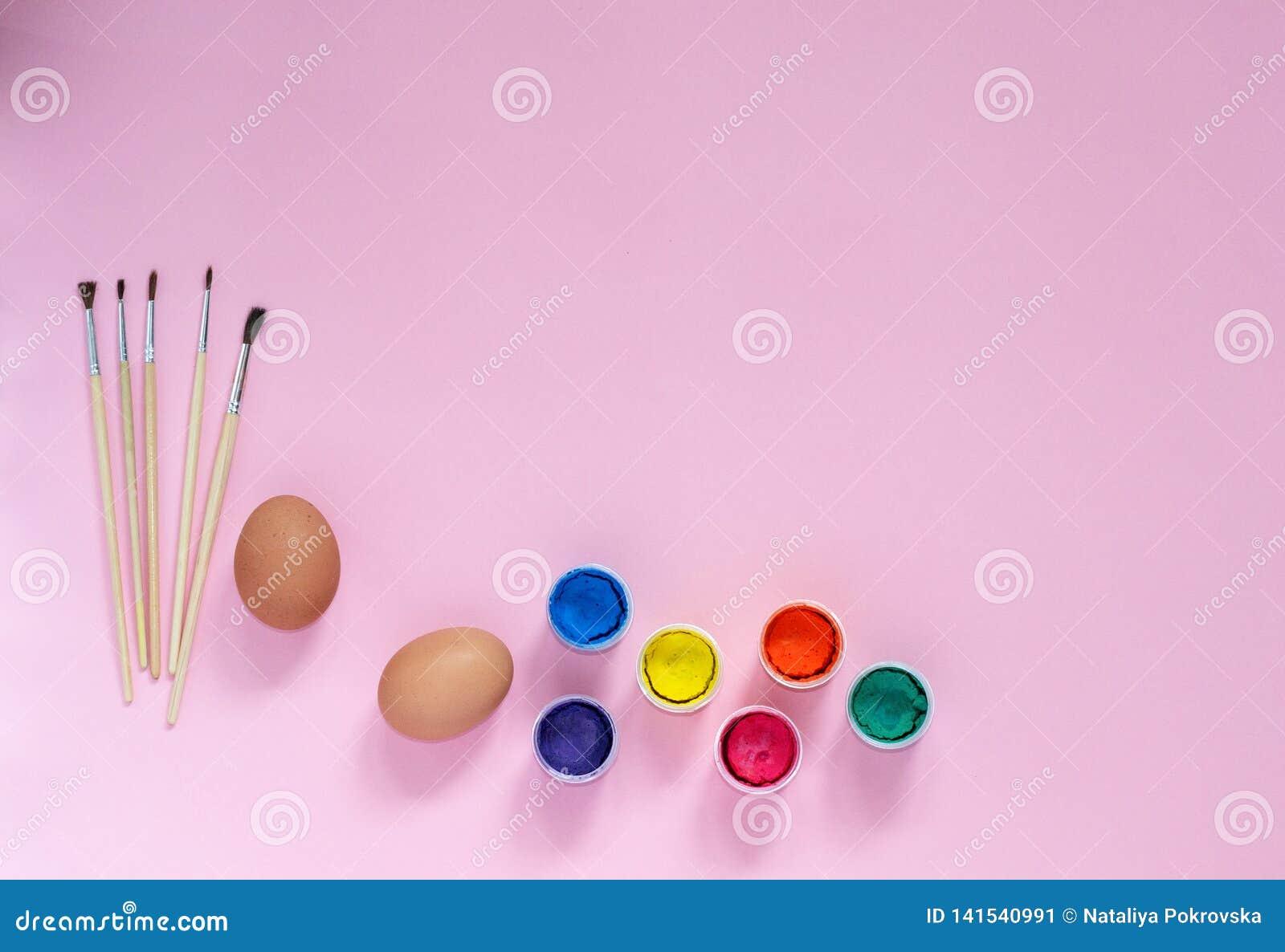 与绘画、刷子和鸡鸡蛋的复活节构成为上色在与copyspace的桃红色做准备从顶视图