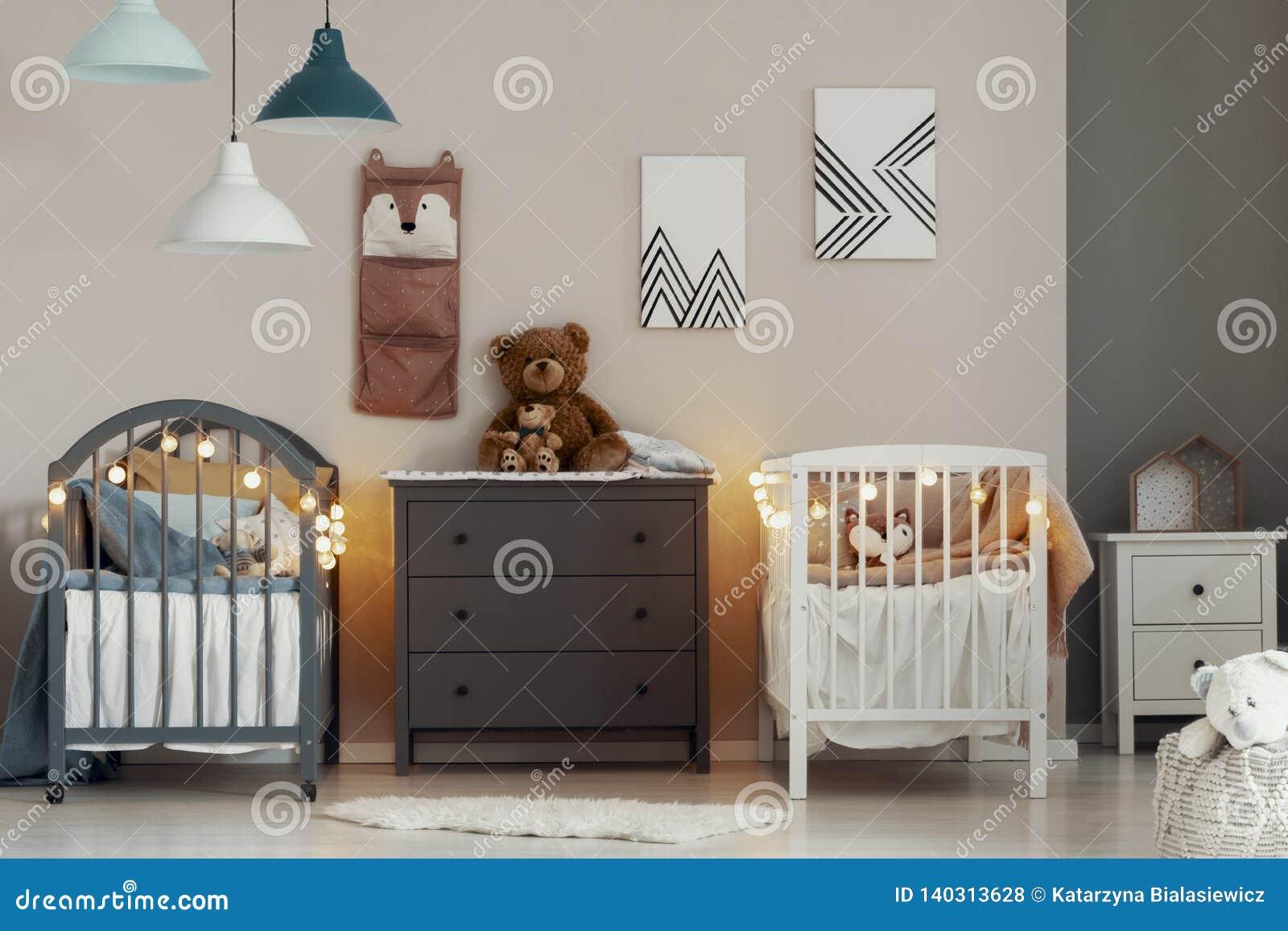 与白色和灰色小儿床、洗脸台和小nightstand桌的舒适婴孩卧室内部