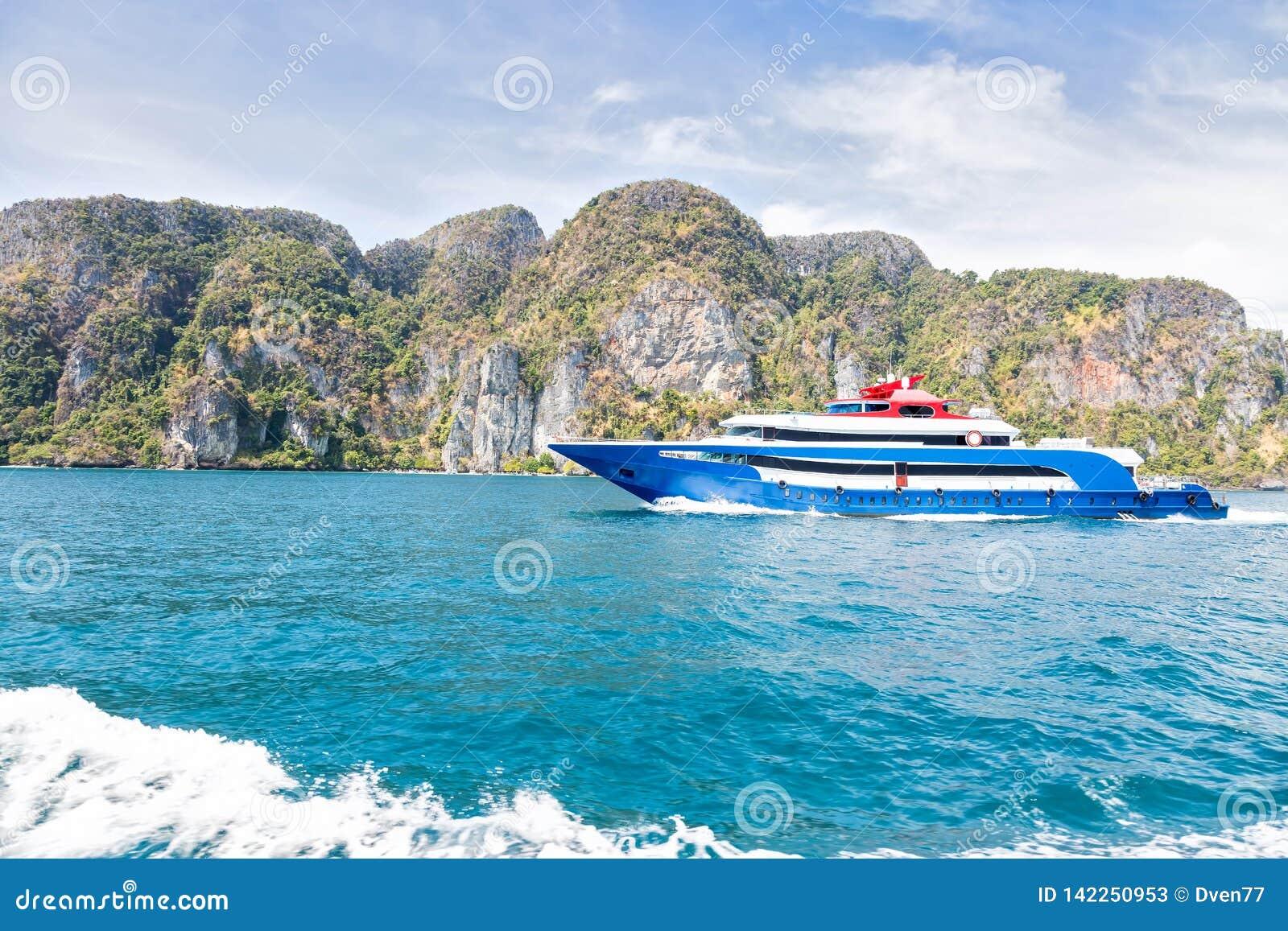 与白色和红色口音乐趣速度小船的蓝色 在海的航行反对一个热带山海岛 侧视图 马达轨道