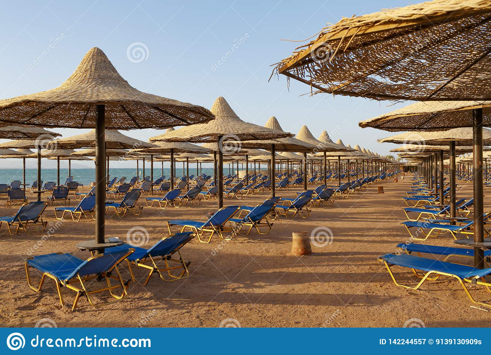 与sunbeds的海滩在海滨的秸杆沙滩伞下