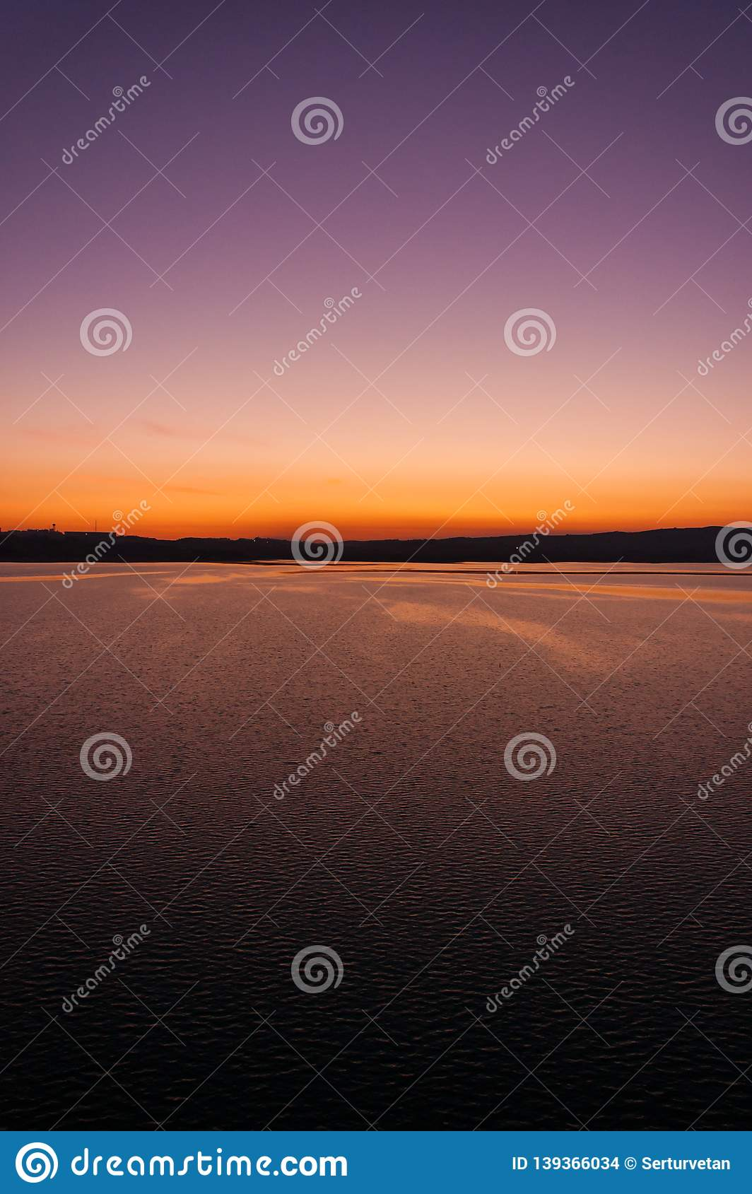 一个华美的颜色和对比在湖日落的 垂直的框架