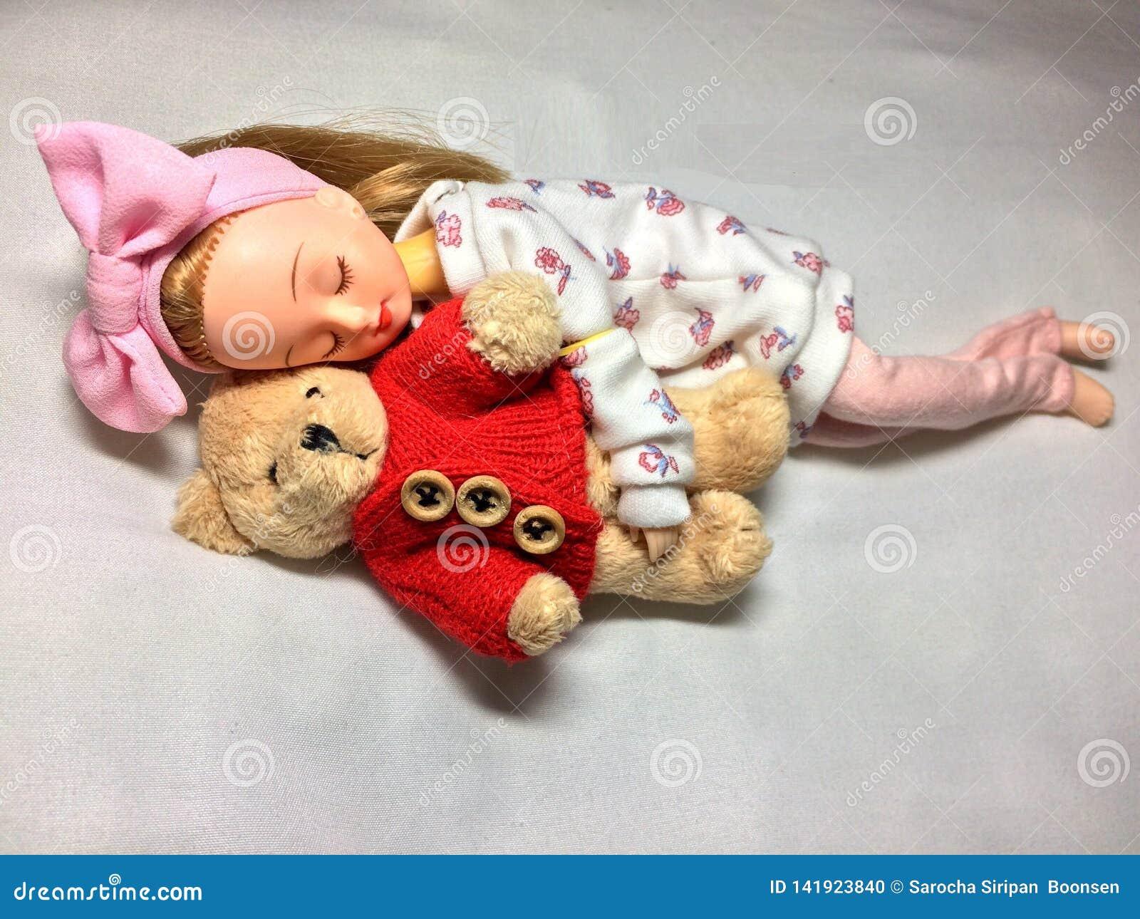 一个可爱的日本玩偶与她的玩具熊睡觉