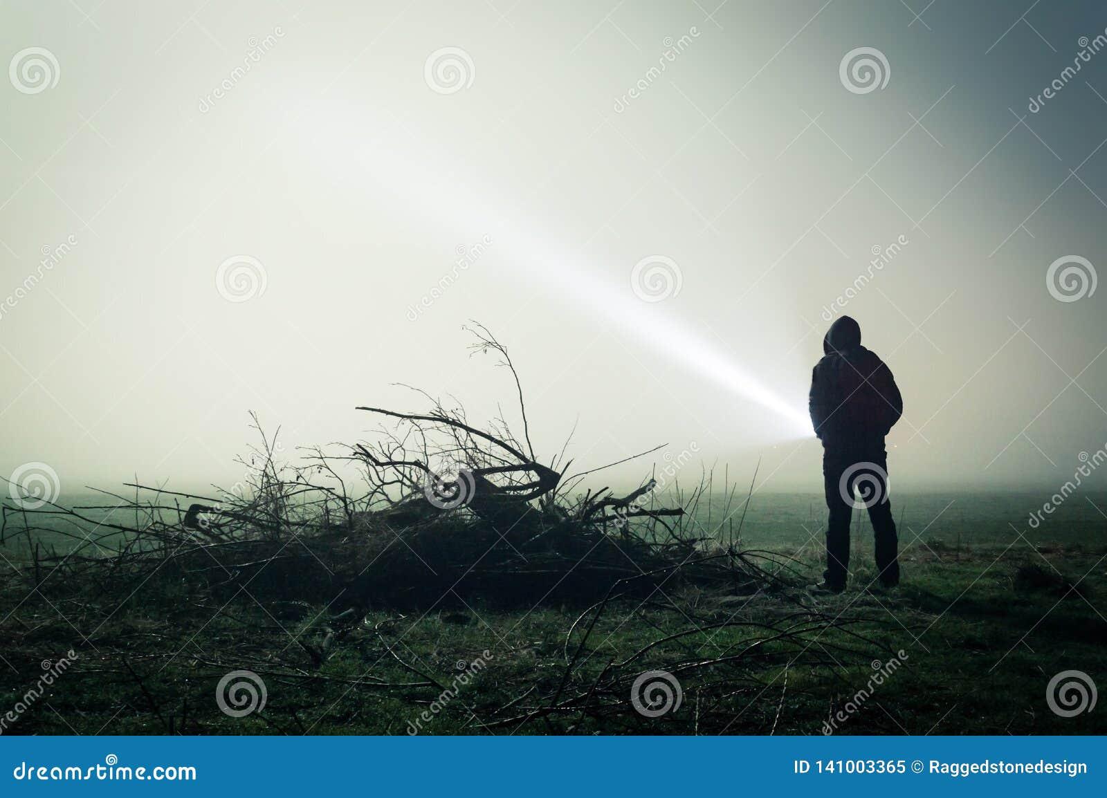 一个孤立戴头巾图的一个令人毛骨悚然的剪影在领域的在与火炬的有雾的夜 以黑暗编辑