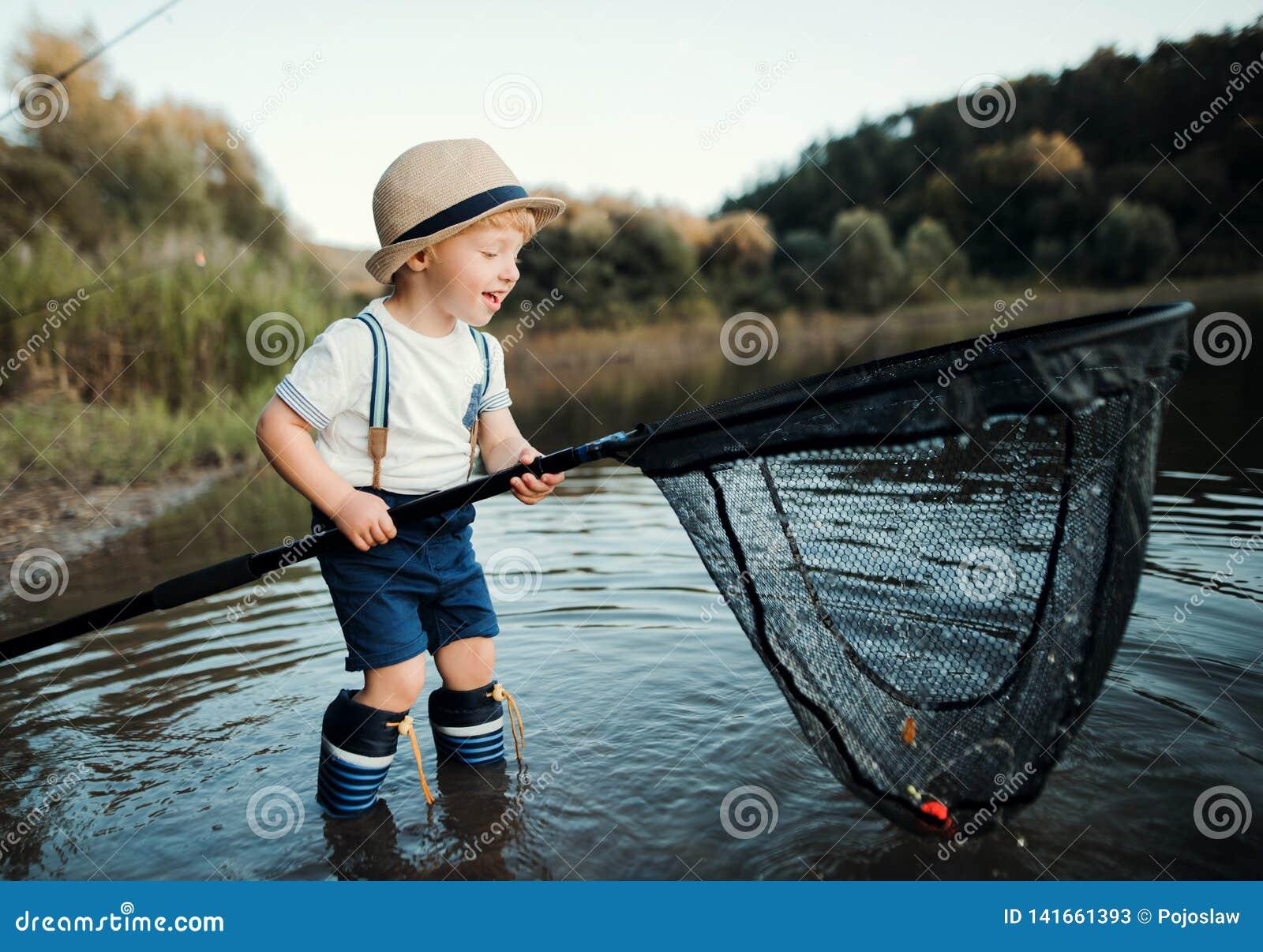 一个小小孩男孩身分在水中和拿着由湖的网,钓鱼