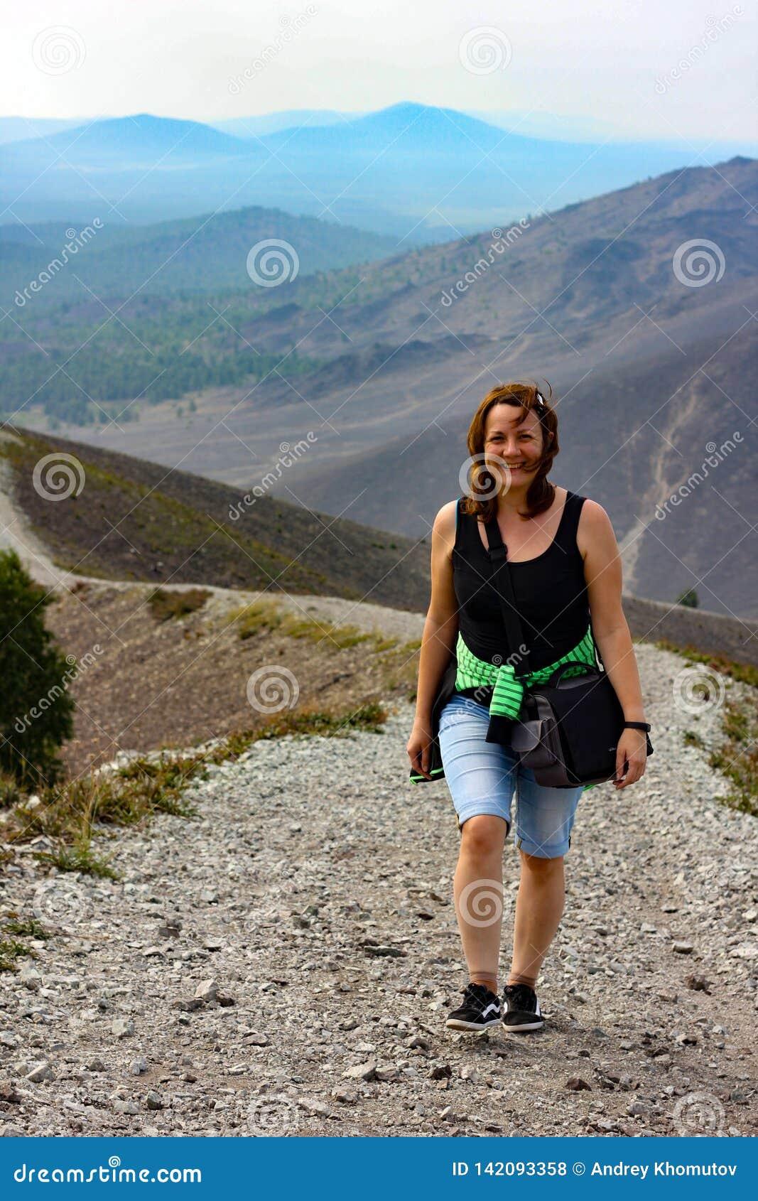 一个愉快的妇女旅客沿山的长的土坎起来上升