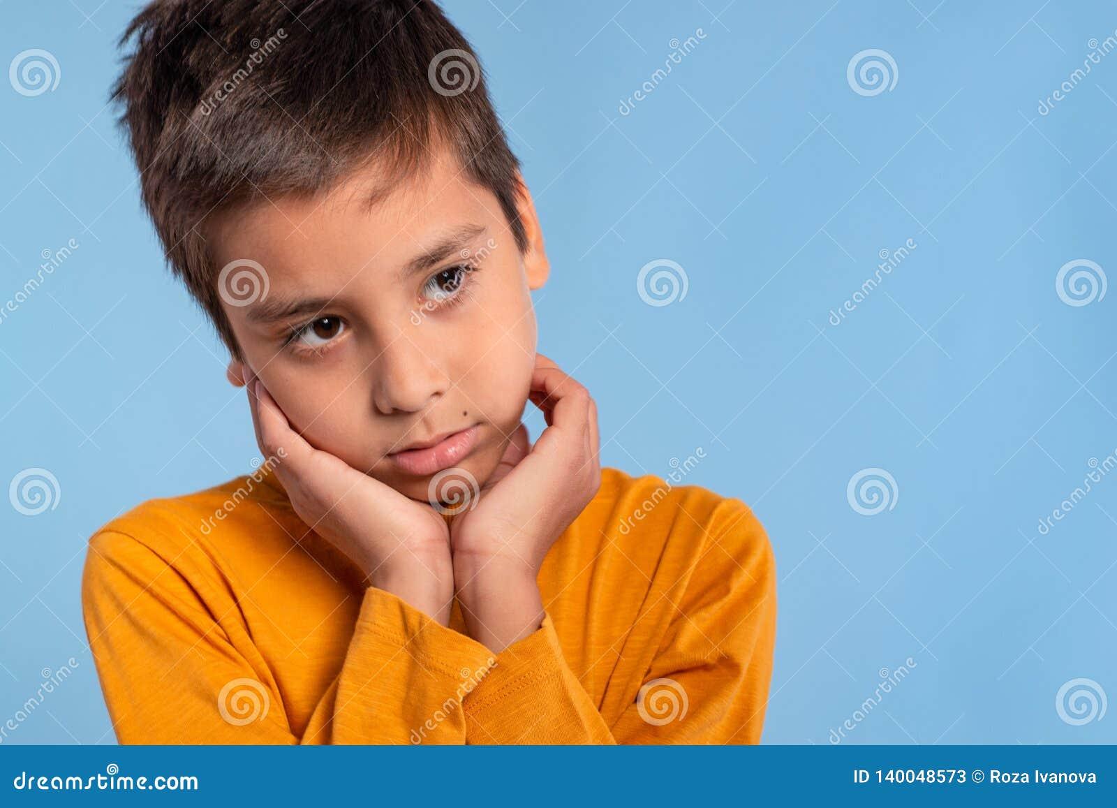 一个男孩的演播室情感射击一件黄色衬衣的在与拷贝空间的蓝色背景 他接触他的面颊棕榈和