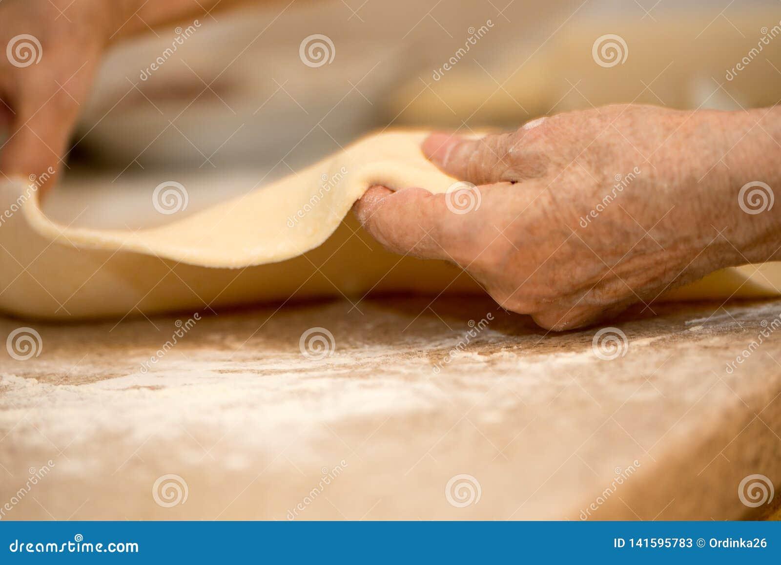 一个老妇人的手铺开面团特写镜头宏指令
