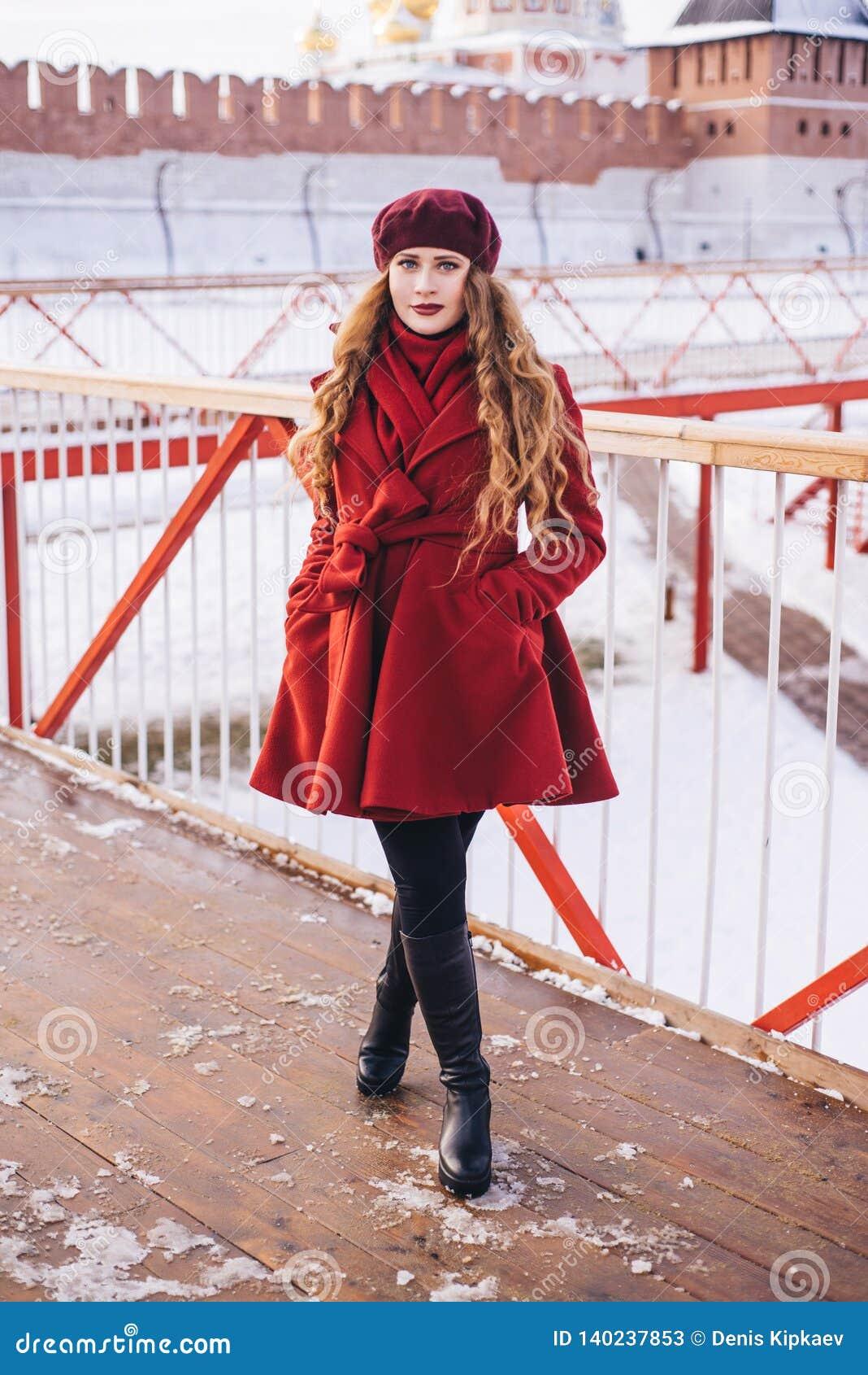 一件红色外套和贝雷帽的一美女沿圣诞节街道走