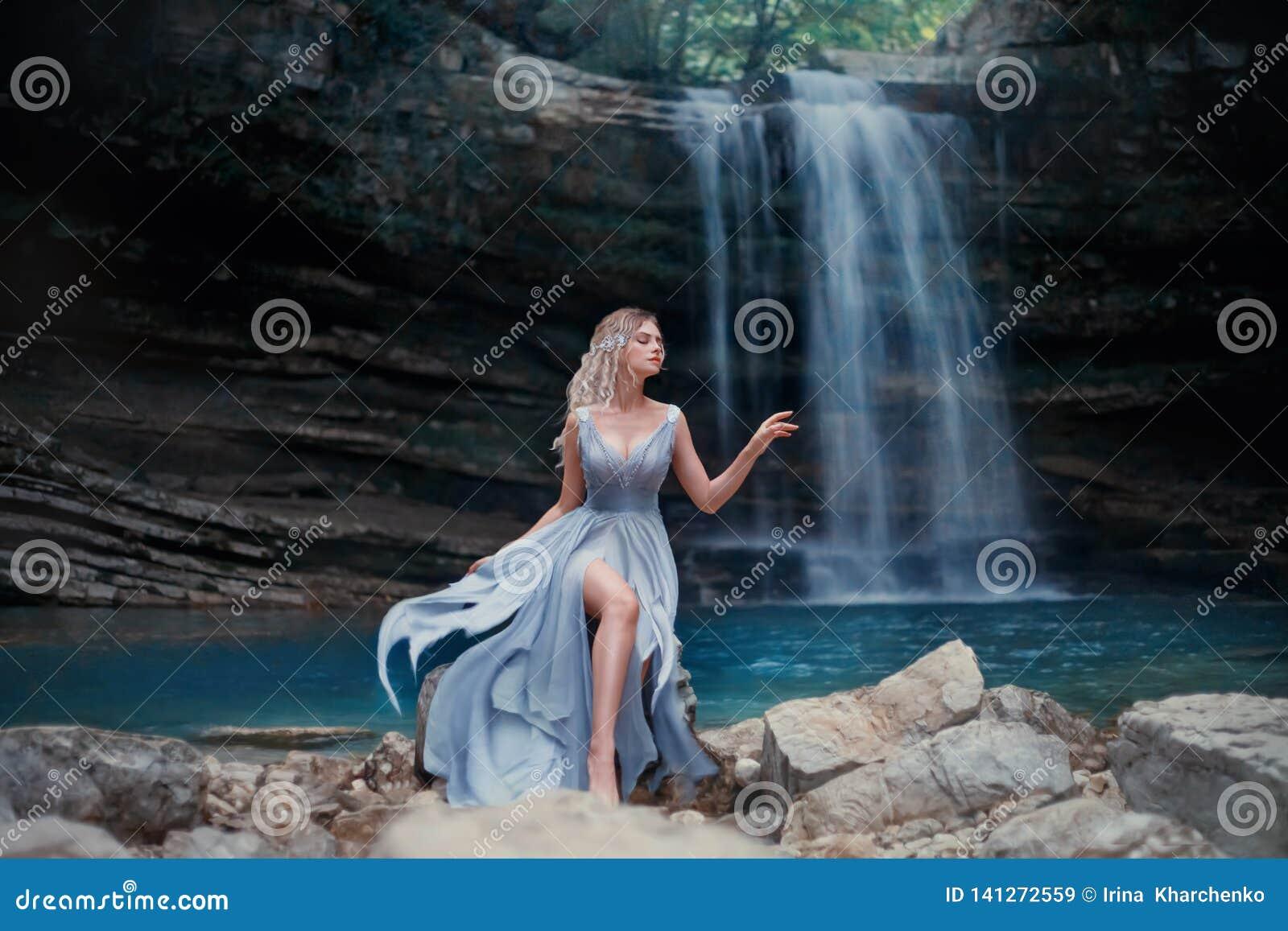 一件豪华蓝色礼服的一个卷曲白肤金发的女孩坐白色石头反对一个美妙的风景的背景 河