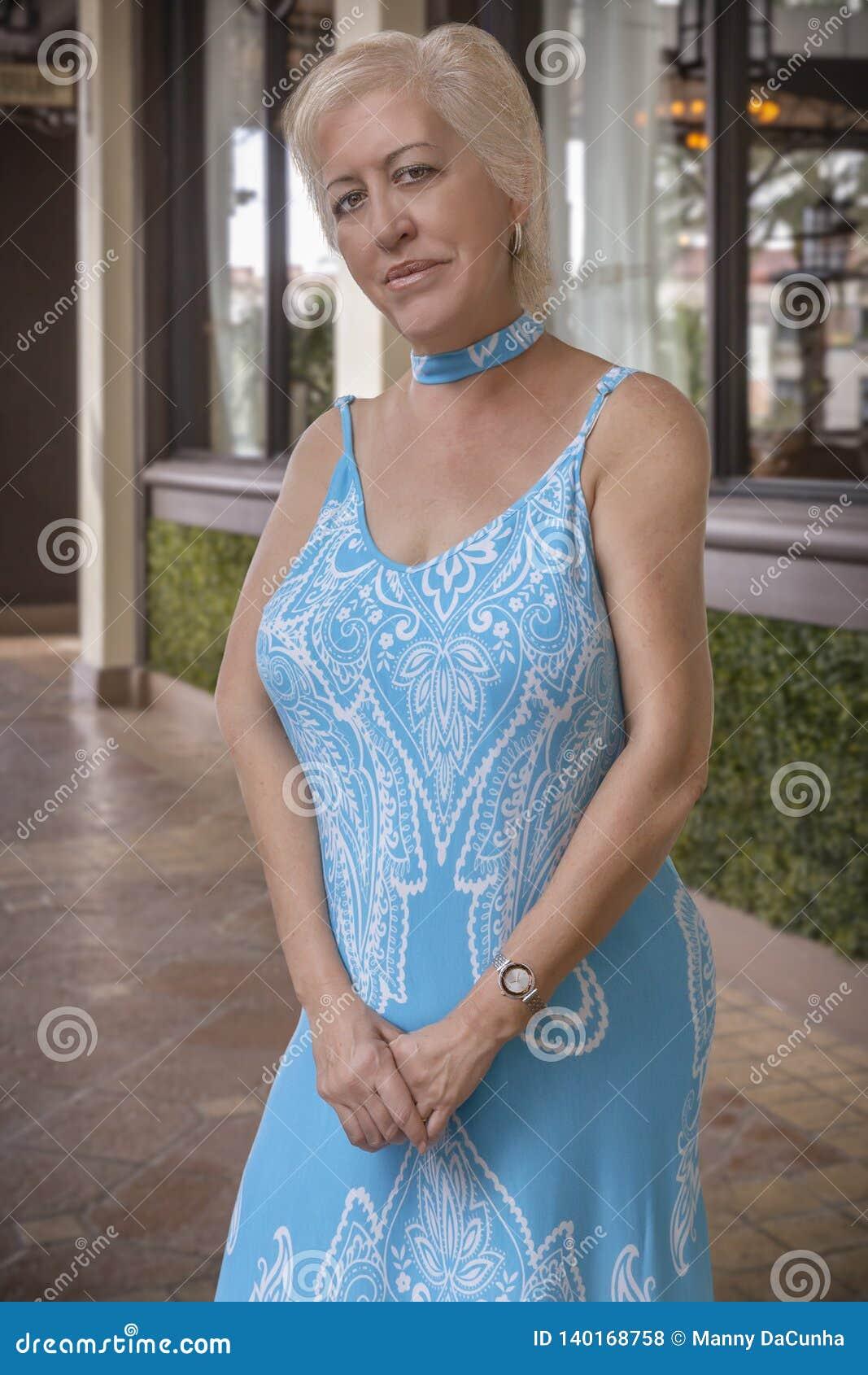 一名在照相机的弯曲的白肤金发的成熟妇女微笑与大美丽的眼睛