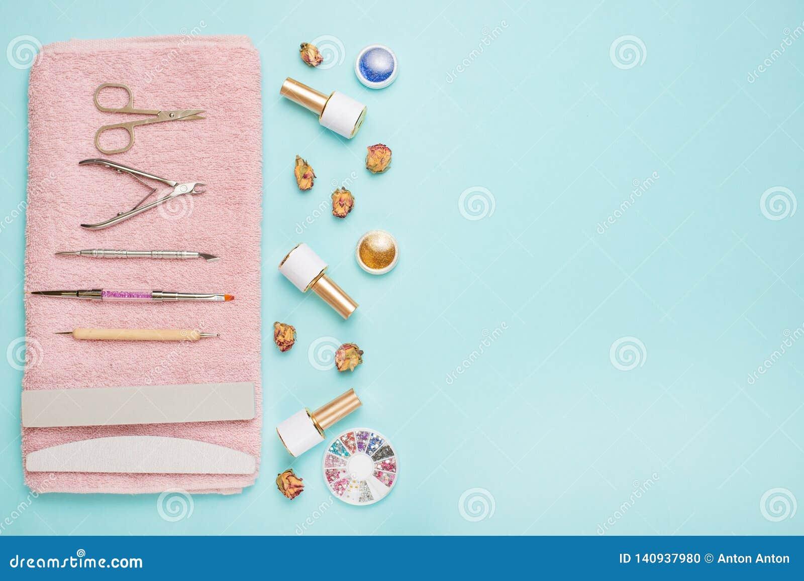 一套为修指甲和修脚的化妆工具在蓝色背景 胶凝体擦亮剂、指甲锉和少年和顶视图