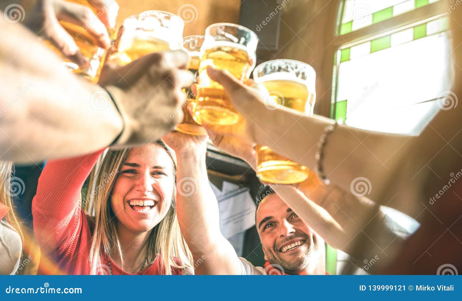 一起喝和敬酒啤酒的朋友在啤酒厂酒吧餐馆-在获得年轻millenial的人民的友谊概念乐趣