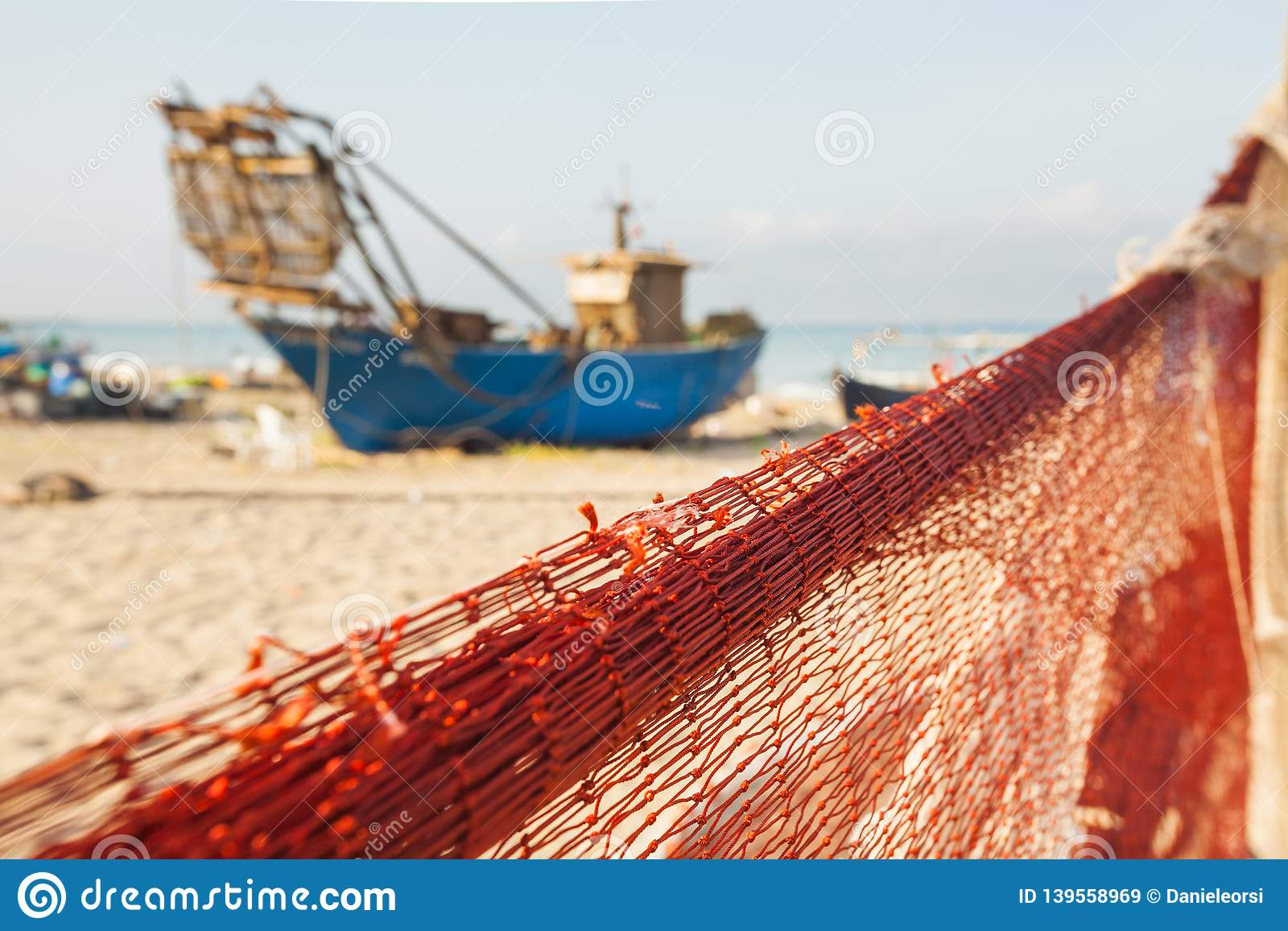 一鱼网的看法在小船前面的在海滩 在一个热的夏日期间,美丽的风平浪静和水