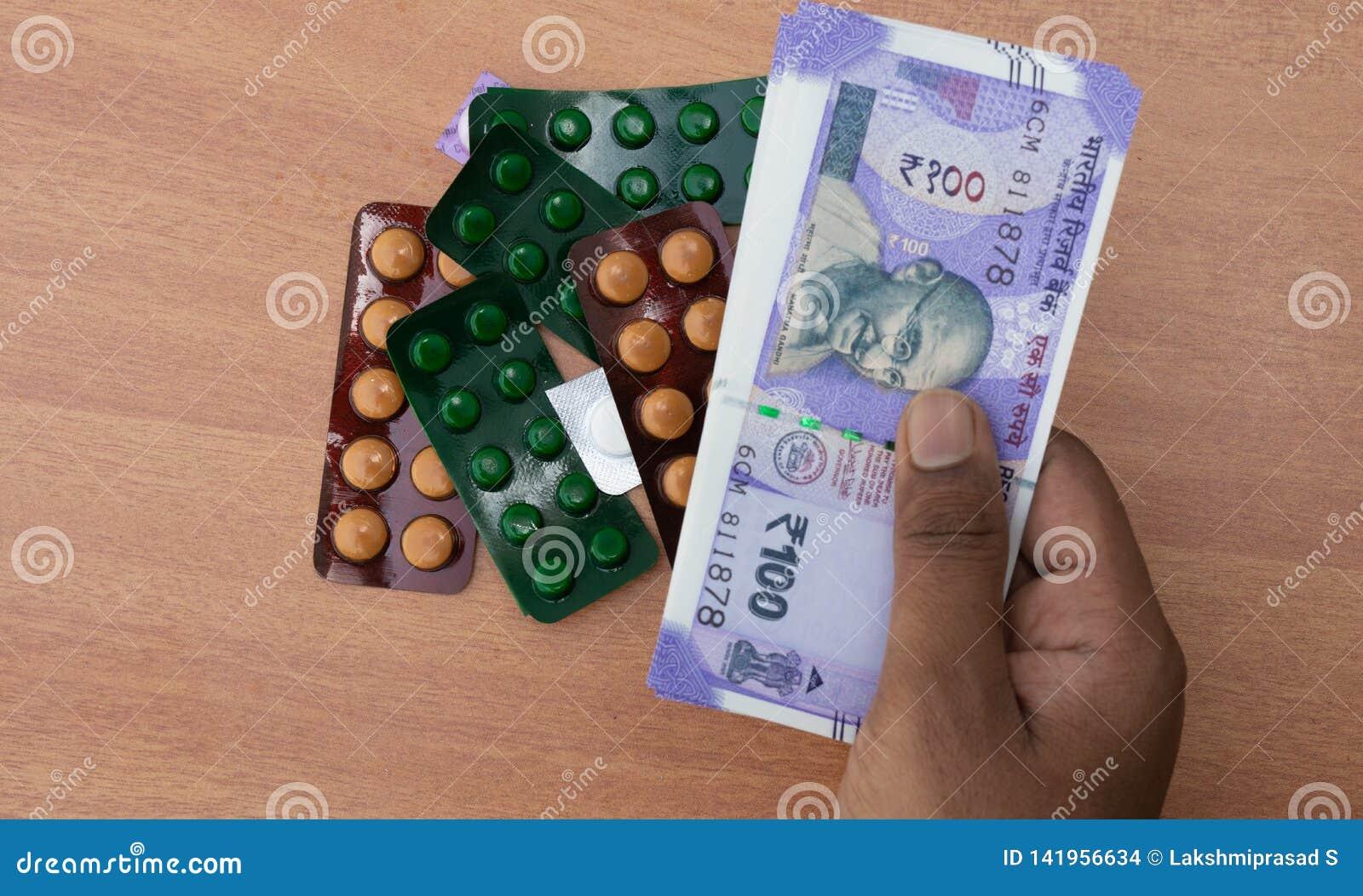 买药片或片剂有印度货币的人的手的概念