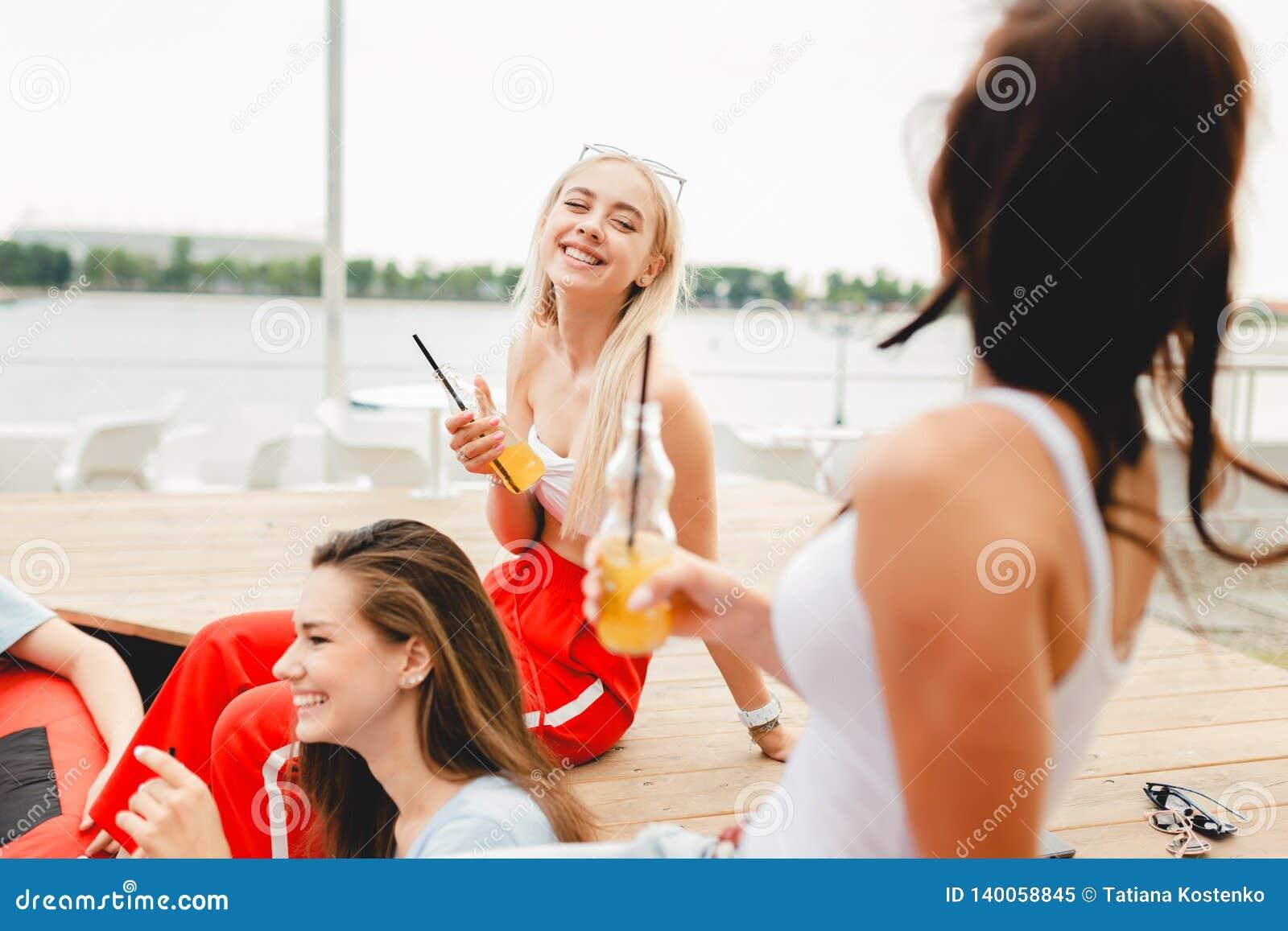 交往悦目的朋友笑,饮用的黄色鸡尾酒公司和,当坐长凳和红色时