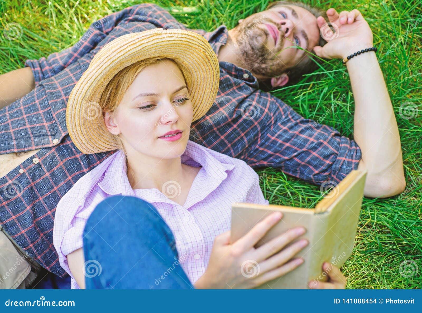 人和女孩在草阅读书放置 夫妇知己在浪漫日期 在爱的夫妇花费休闲看书