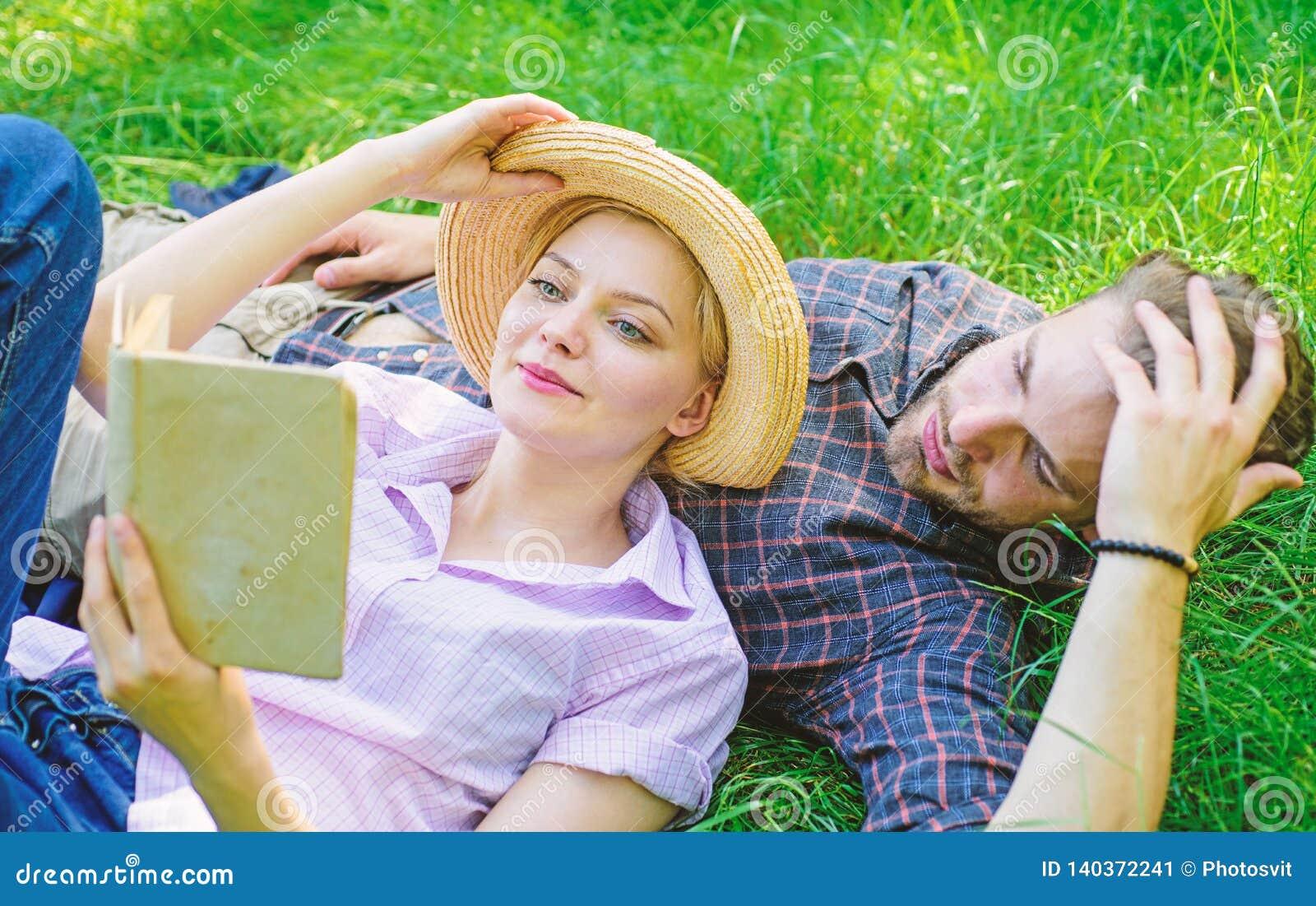 人和女孩在草阅读书放置 家庭享受休闲有诗歌或文学书草背景 夫妇