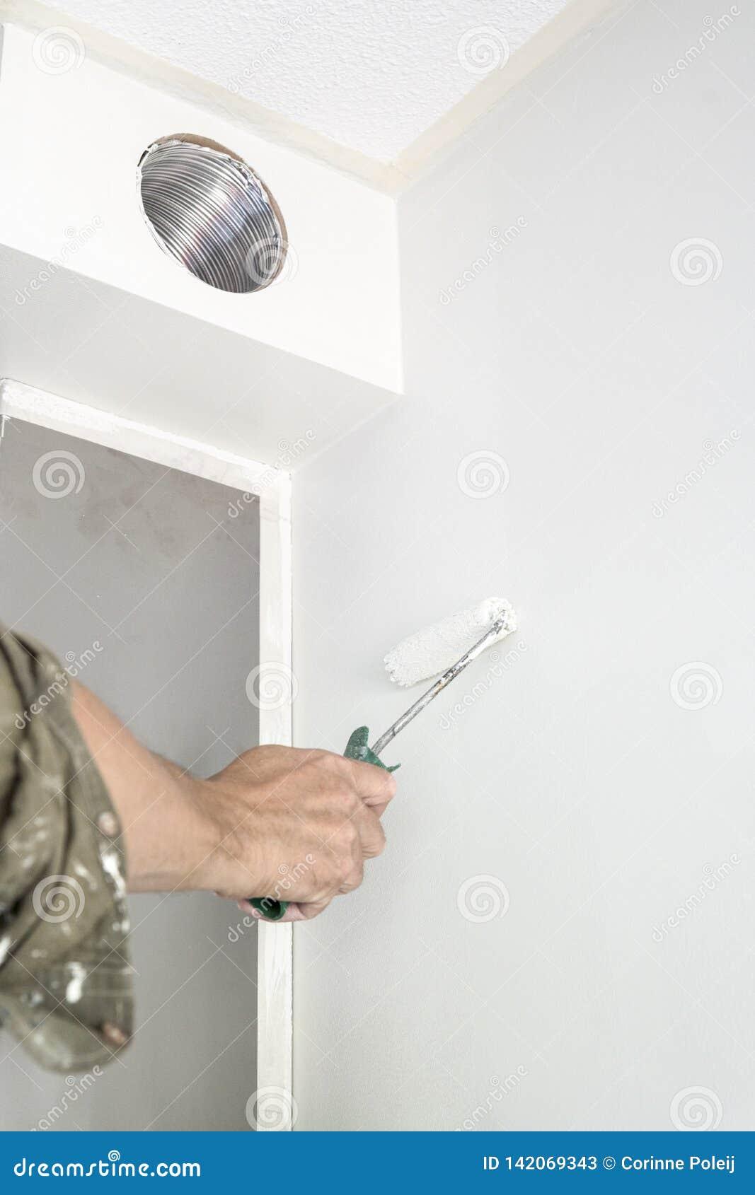 人绘画白色墙壁,有路辗的
