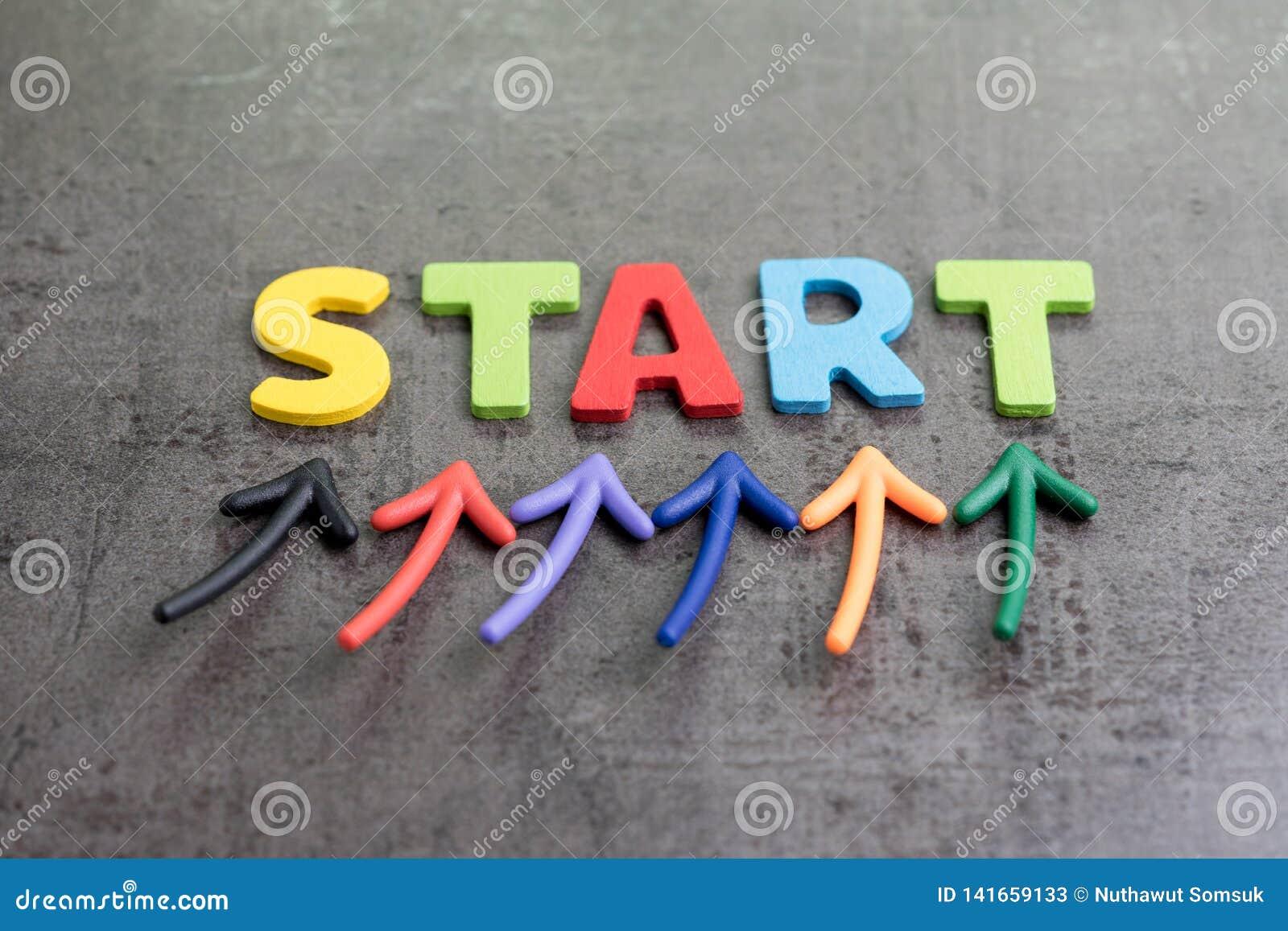 企业开始开始旅途概念,五颜六色的箭头指向由在黑板水泥墙壁上的词开始决定强调
