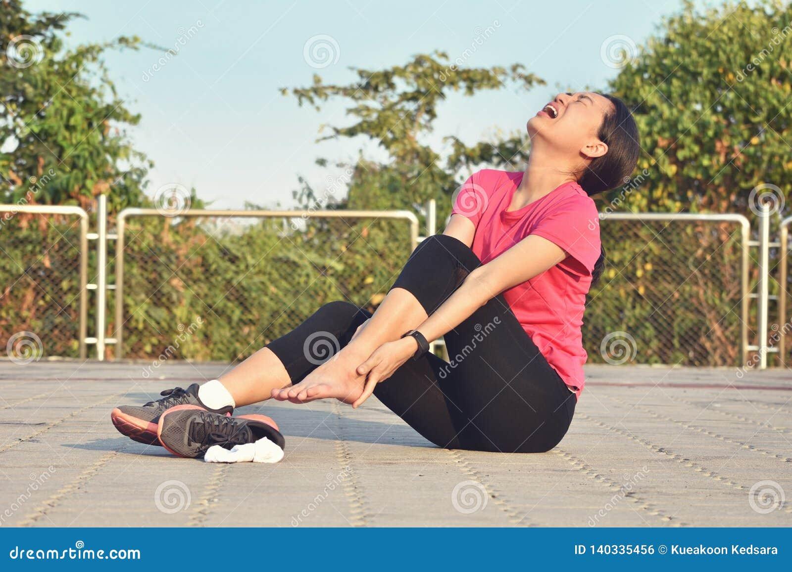 伤害妇女的赛跑者在痛苦中握痛苦的被扭伤的脚腕