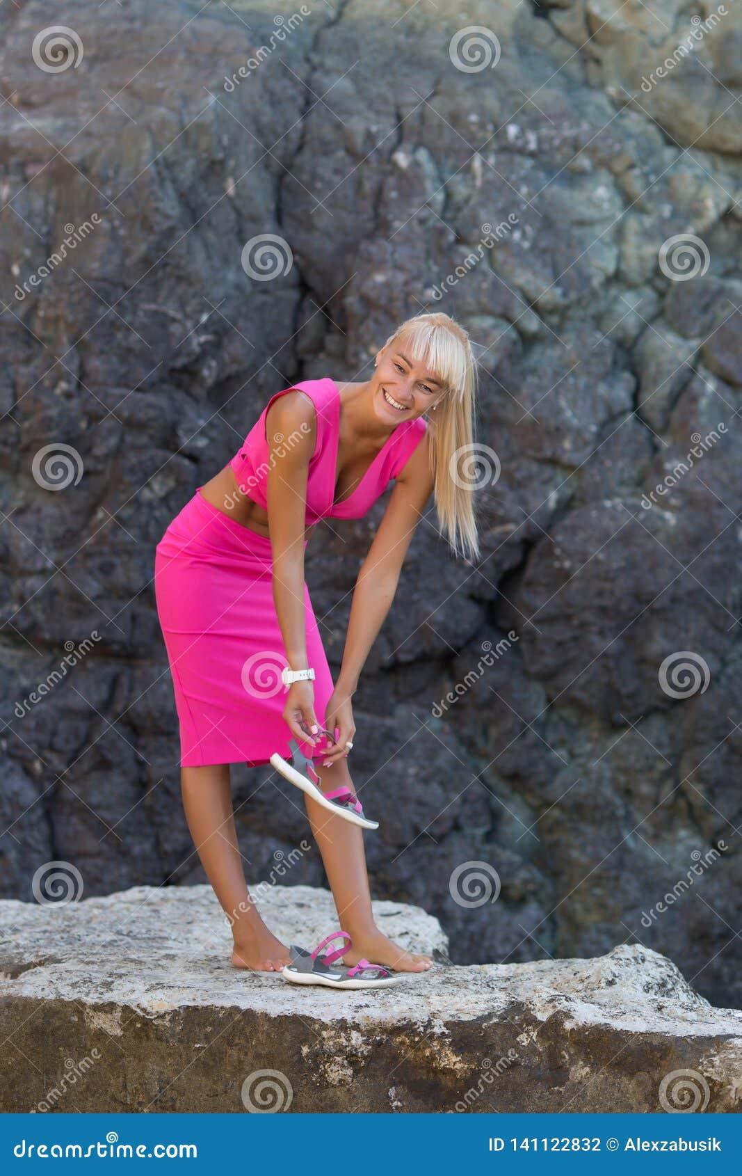 休息在狂放的岩石海滨偏僻的地方的被晒黑的金发女性