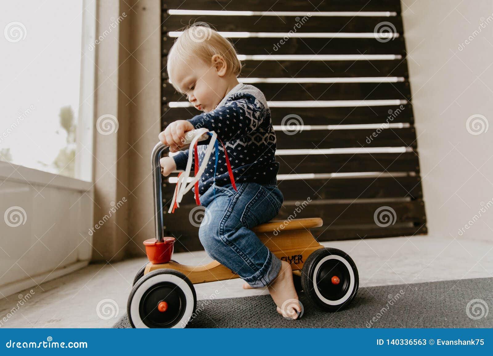 使用外面在木玩具自行车滑行车机动性的珍贵的可爱的逗人喜爱的矮小的白肤金发的小小孩男孩孩子微笑对来了