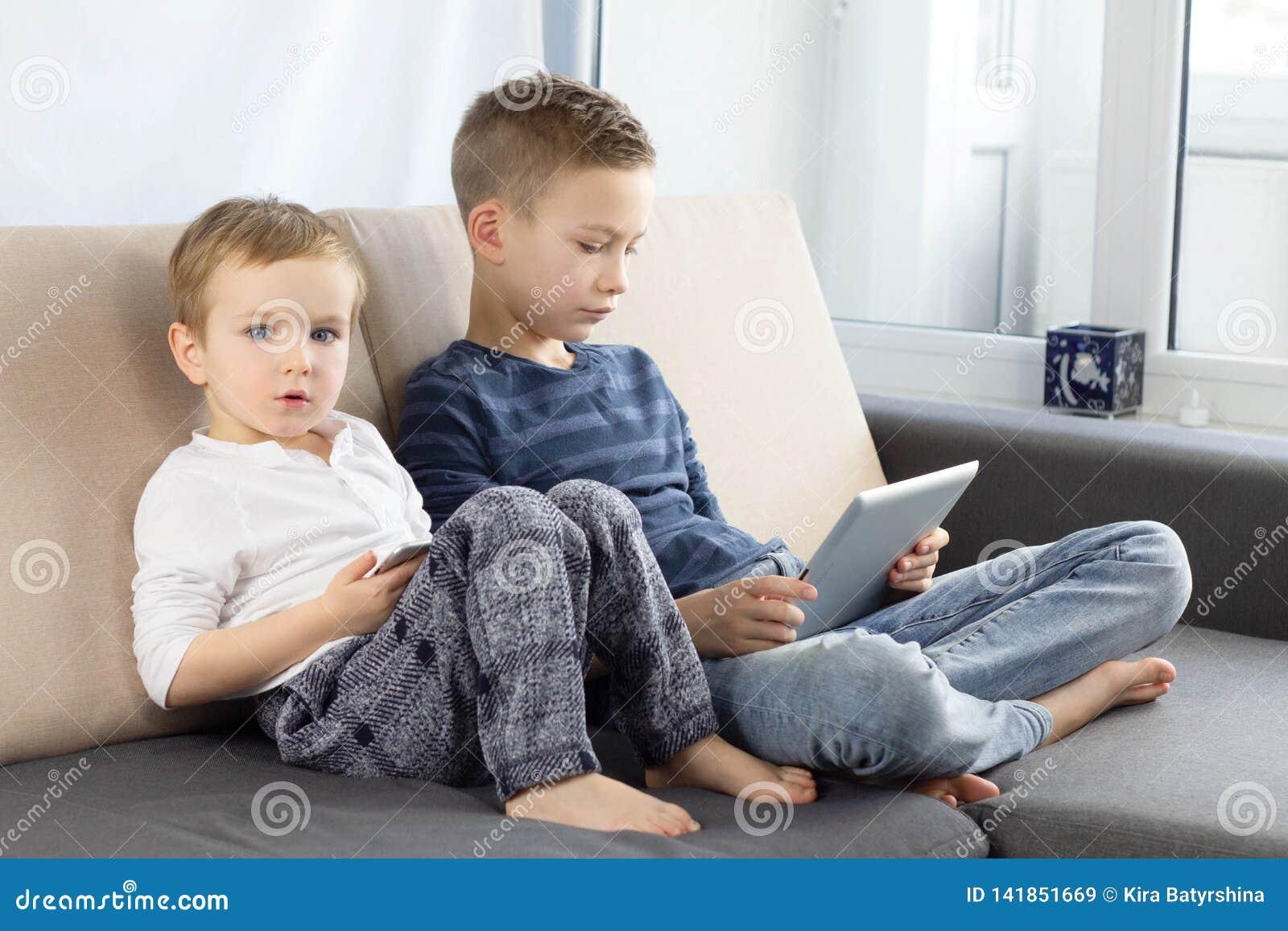 使用小配件的两个孩子在家 有片剂计算机的兄弟在轻的屋子里 打在平板电脑的男孩比赛,情感