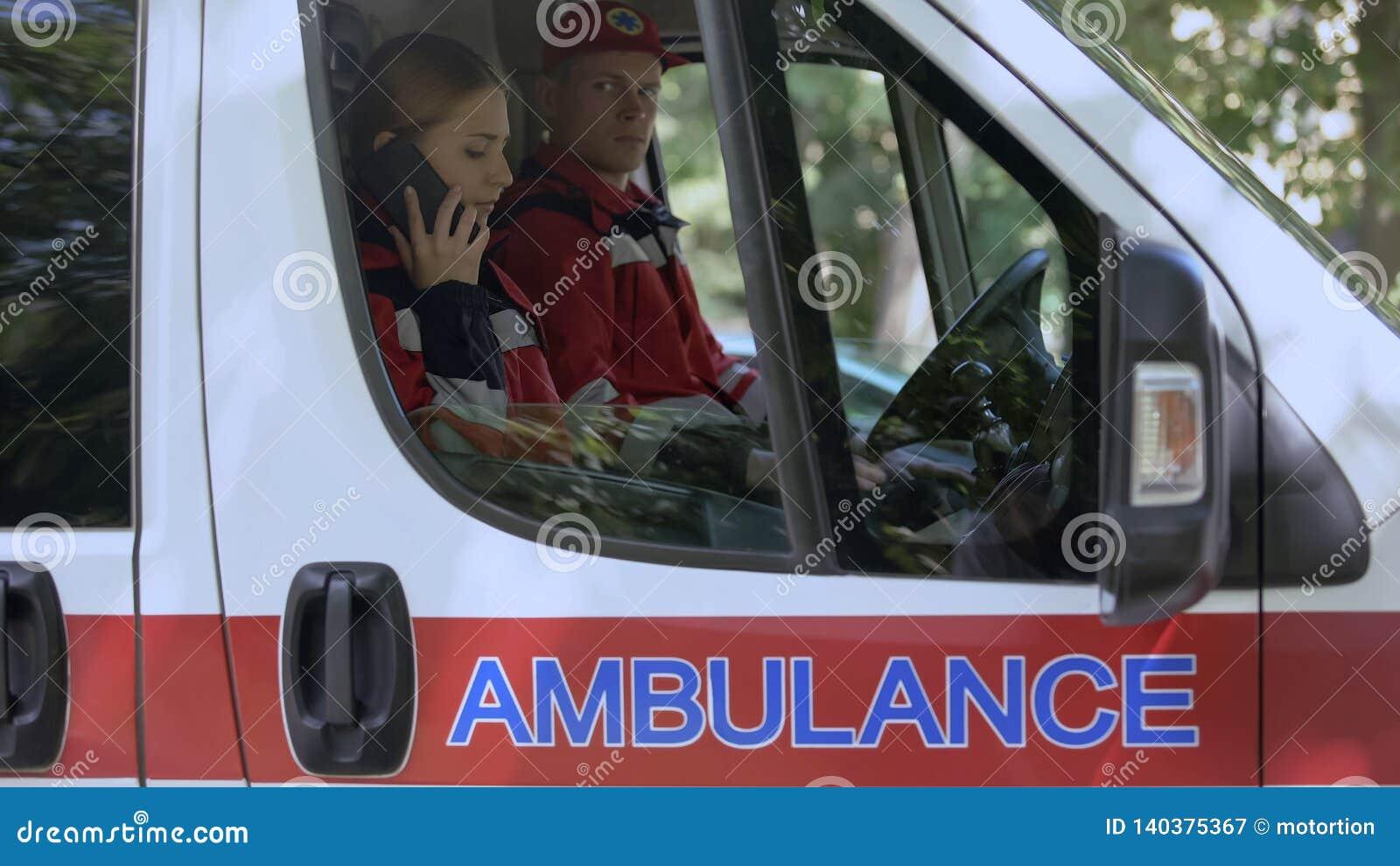 使用智能手机的女性医务人员告诉患者,当班救护车的乘员组