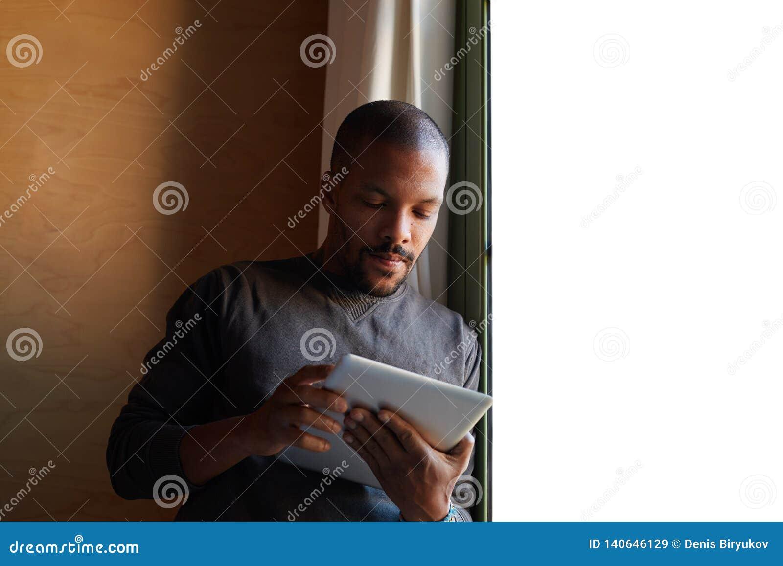 使用片剂在家客厅的典雅的非洲黑人