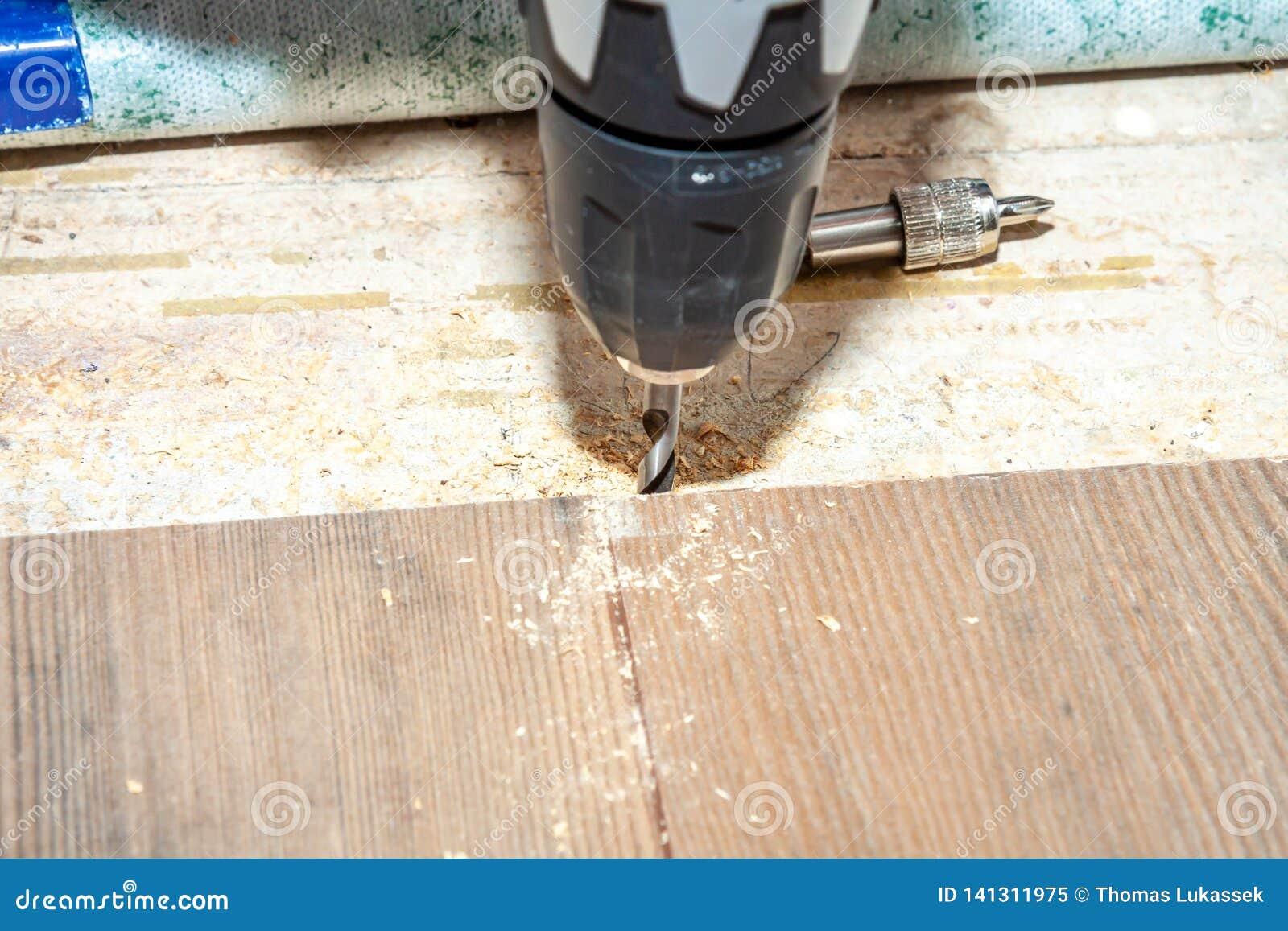 使用钻子机器的人,当在家时安装新的木层压制品的地板