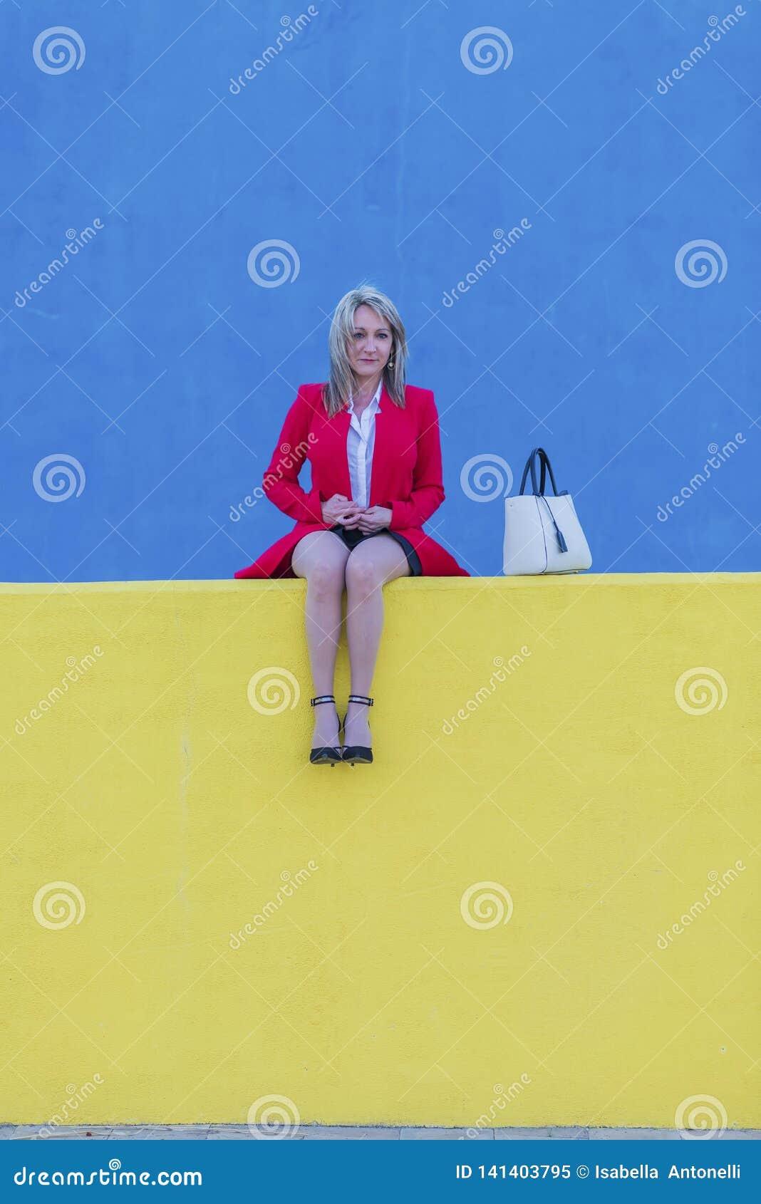 低角度观点的红色夹克的一名典雅的白肤金发的妇女坐长凳户外,当看照相机在好日子时