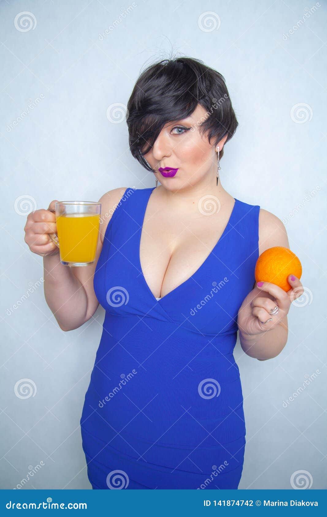 俏丽的胖的浅黑肤色的男人用橙色果子在她的手上和有玻璃杯子的用站立在白色后面的蓝色礼服的健康汁液