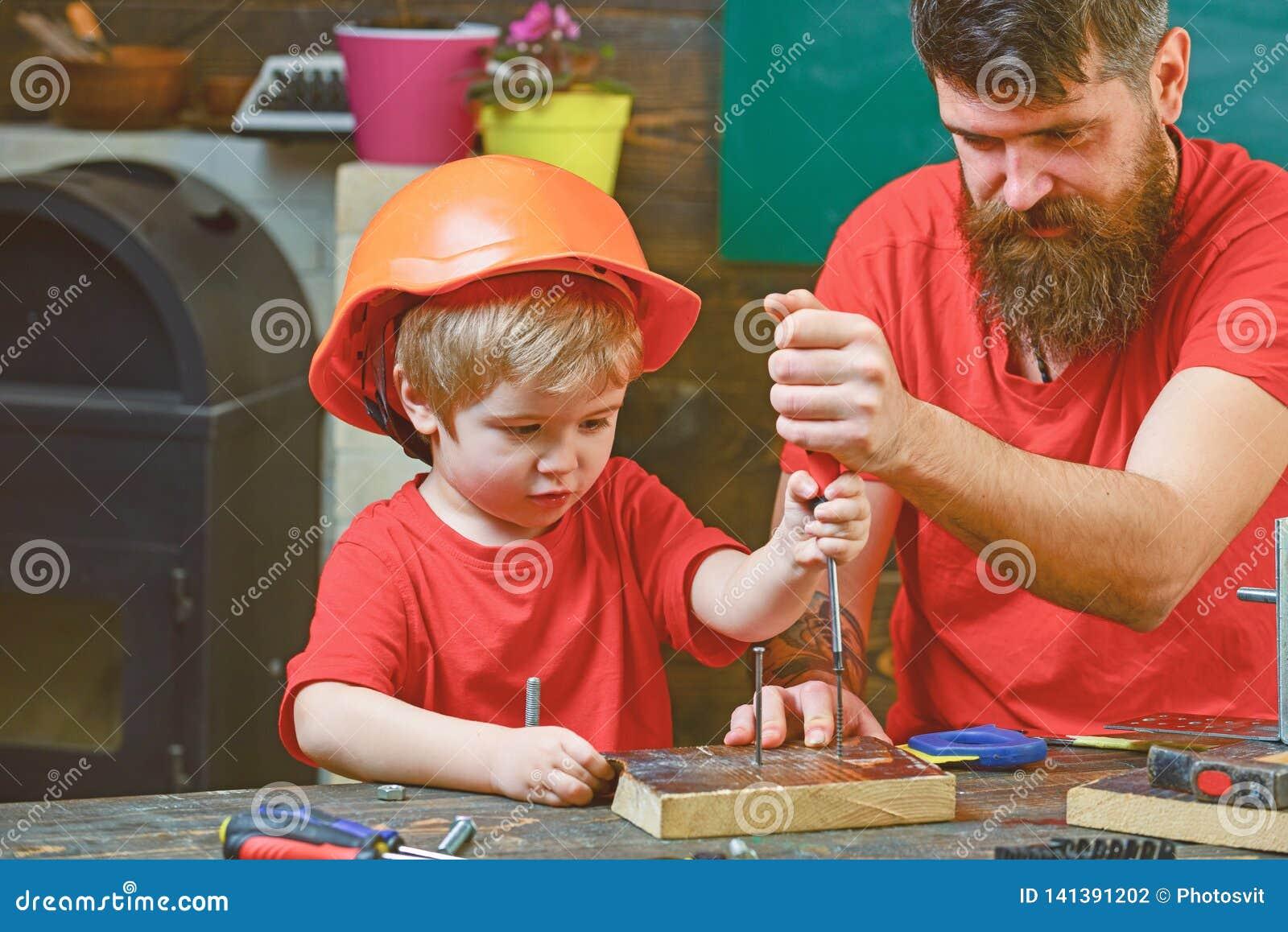 修理和车间概念 男孩,孩子繁忙在防护盔甲学会使用有爸爸的螺丝刀 父亲,父母