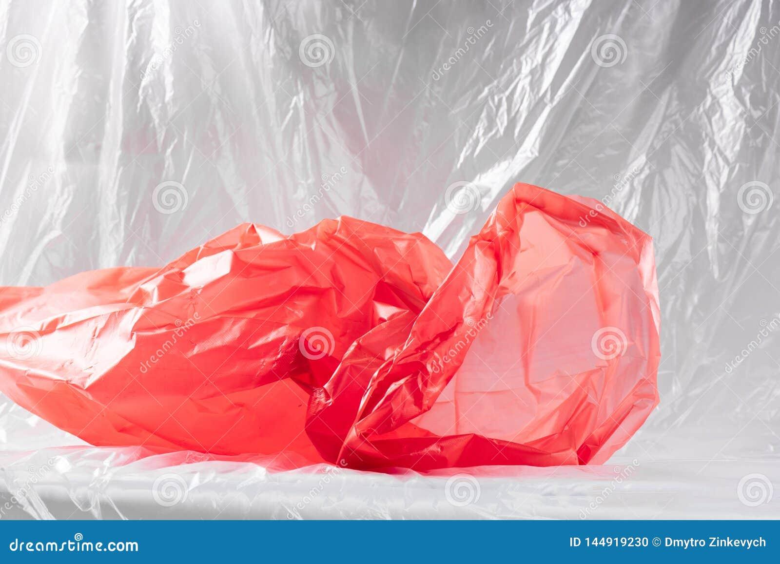 Äckla den skrynkliga röda plast- avfallpacken som framlägger tillståndet av vår natur